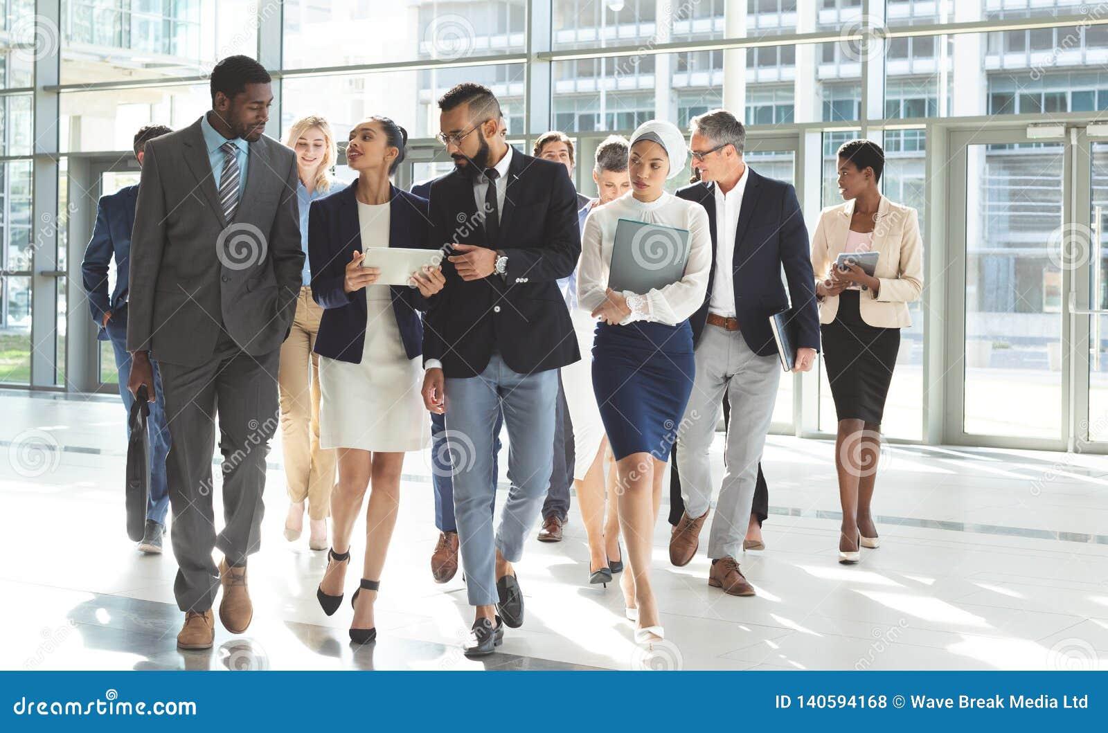Främre sikt av gruppen av olikt affärsfolk som tillsammans går i lobbykontor