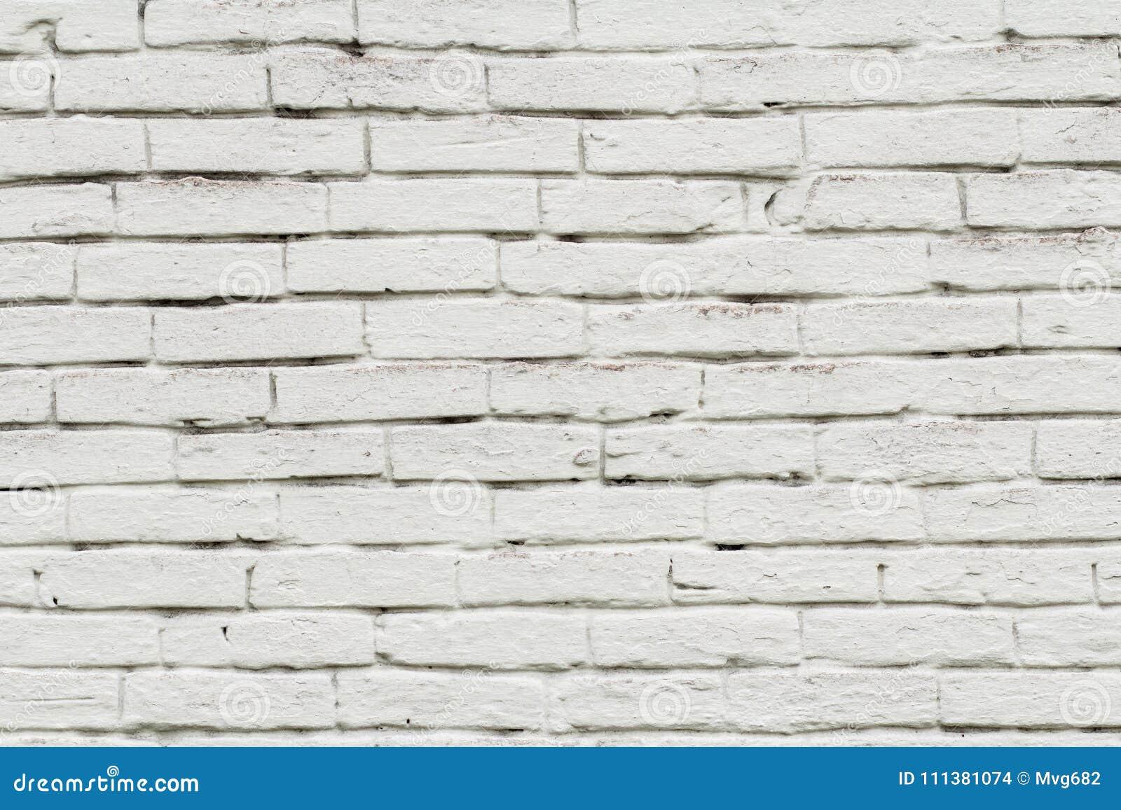 Främre sikt av tegelstenväggen som målas i vit färg