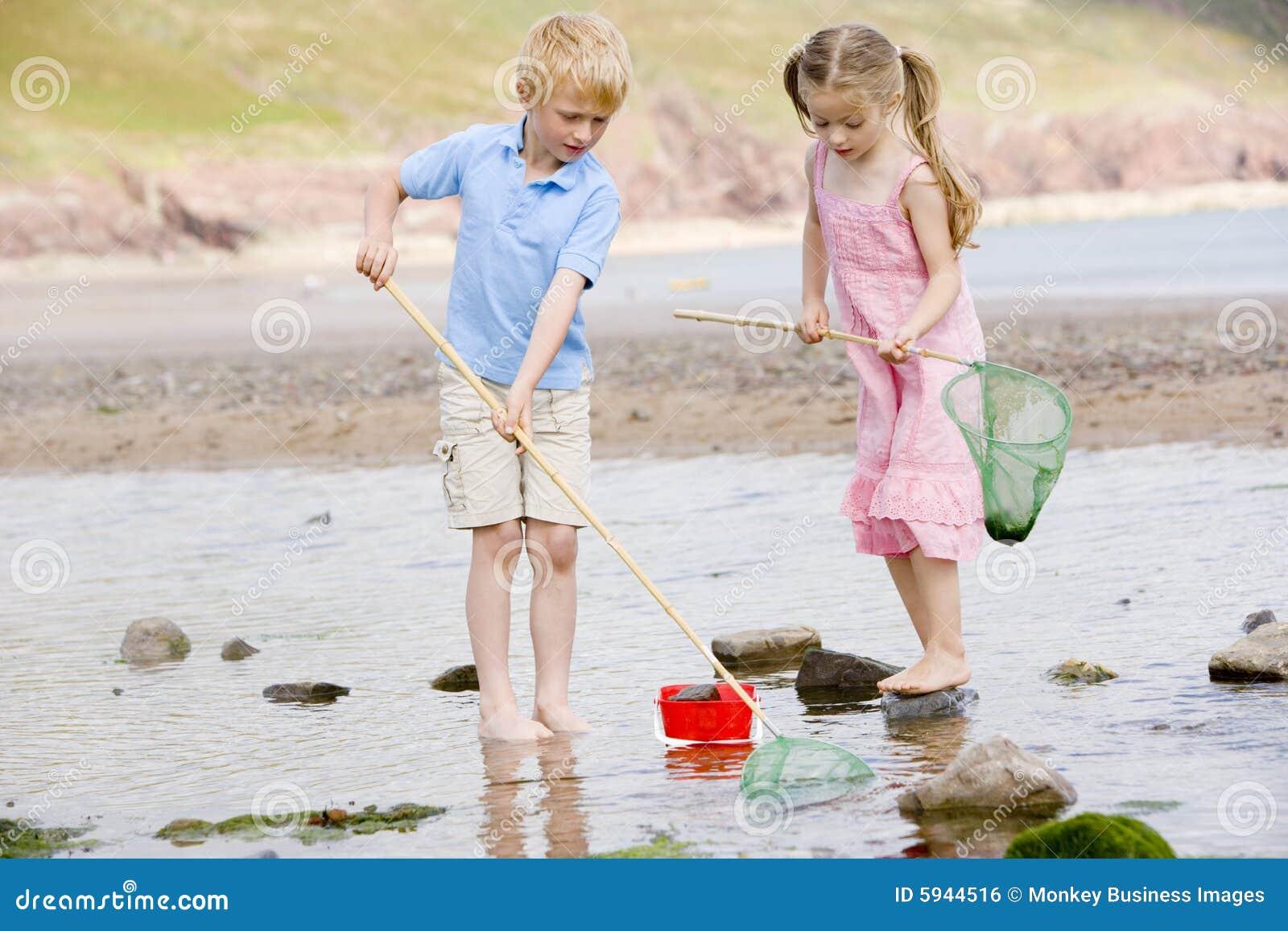 Frère et soeur à la plage avec les réseaux et le seau