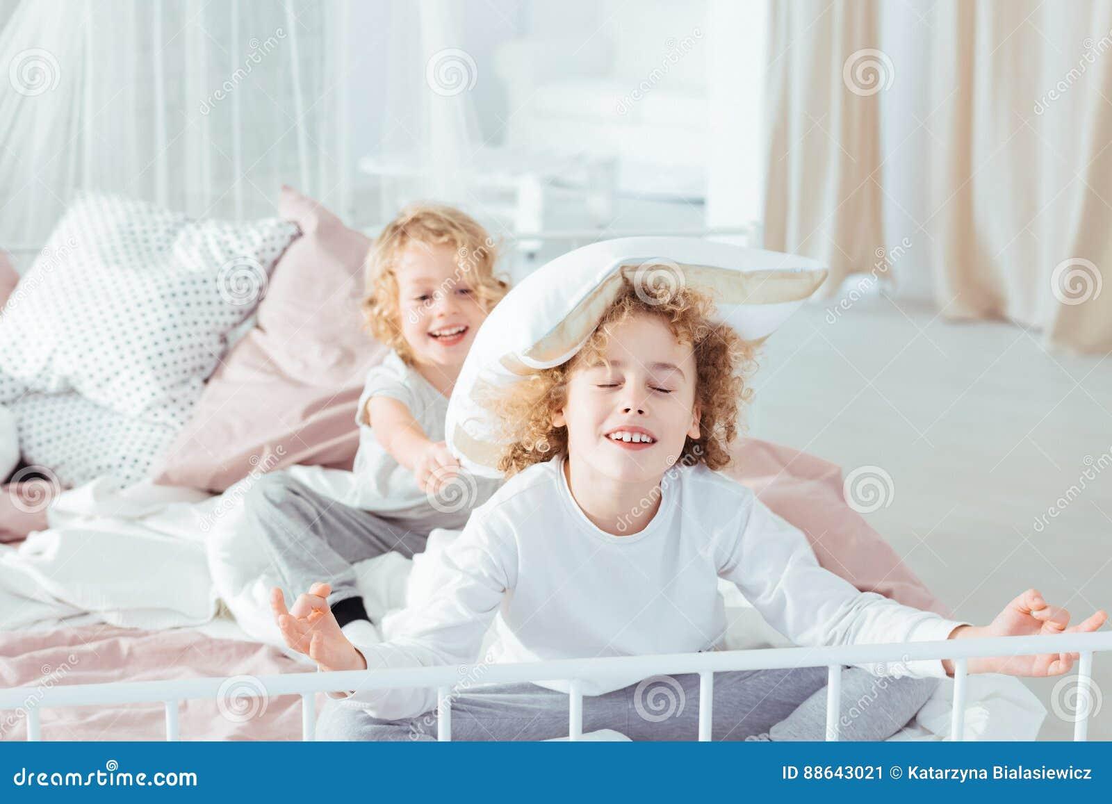 Frères ayant le combat d oreiller de matin