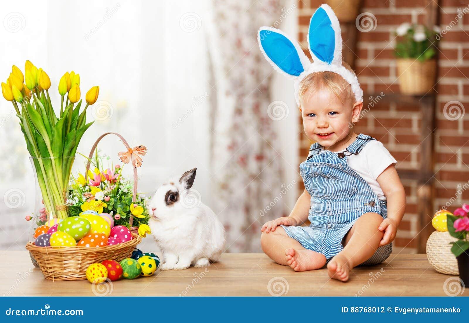 Fröhliche Ostern! glückliches lustiges Baby, das mit Häschen spielt