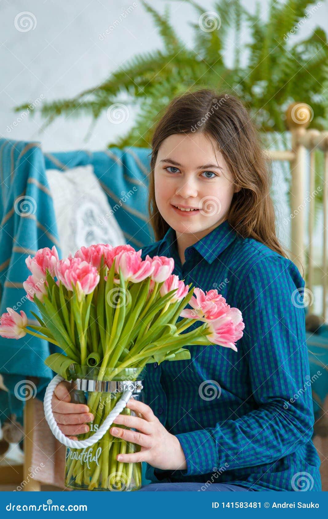 Frühlingsporträt eines Mädchens mit rosa Tulpen