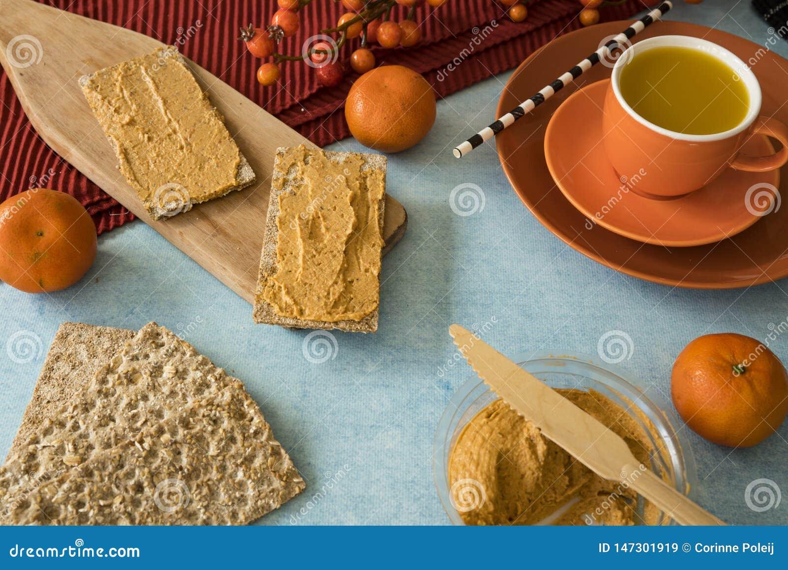 Frühstück mit hummus auf Toast, mit Mandarinen und Orangensaft