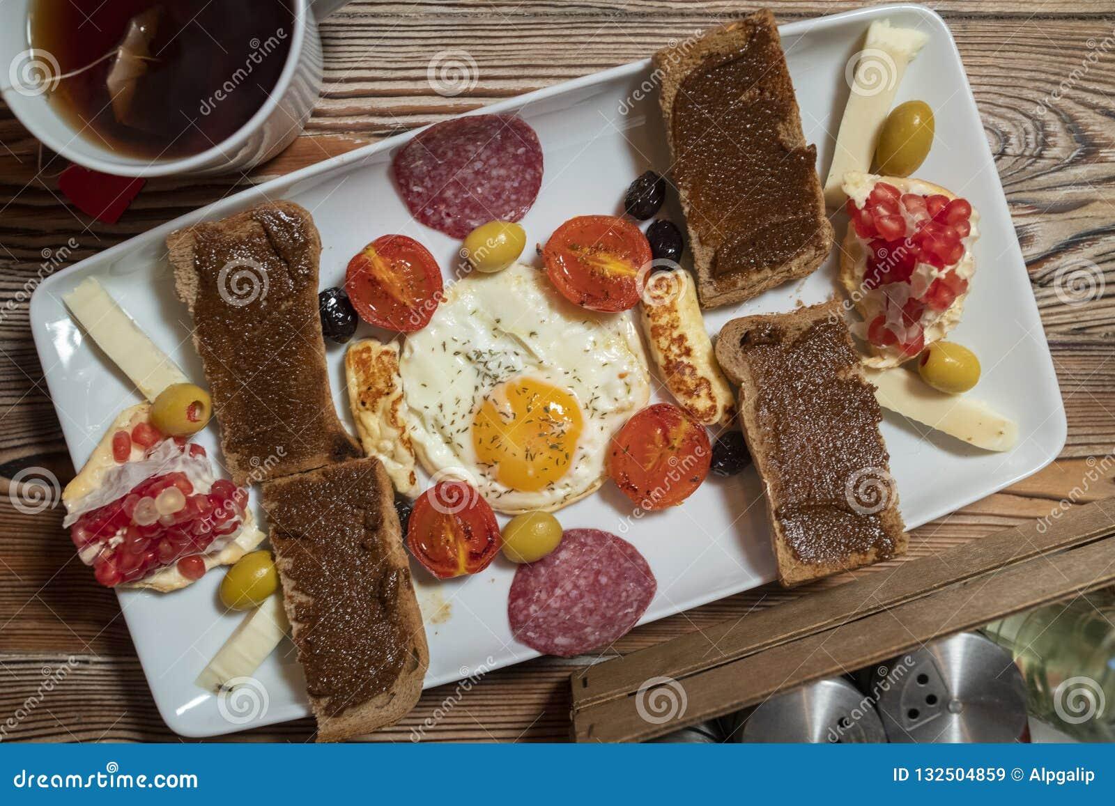Frühstück mit Spiegelei, Roggenbrot, Granatapfel, Johannisbrotbaumpaste, Käsen, Oliven, trockener Salami, Tomaten und Tee