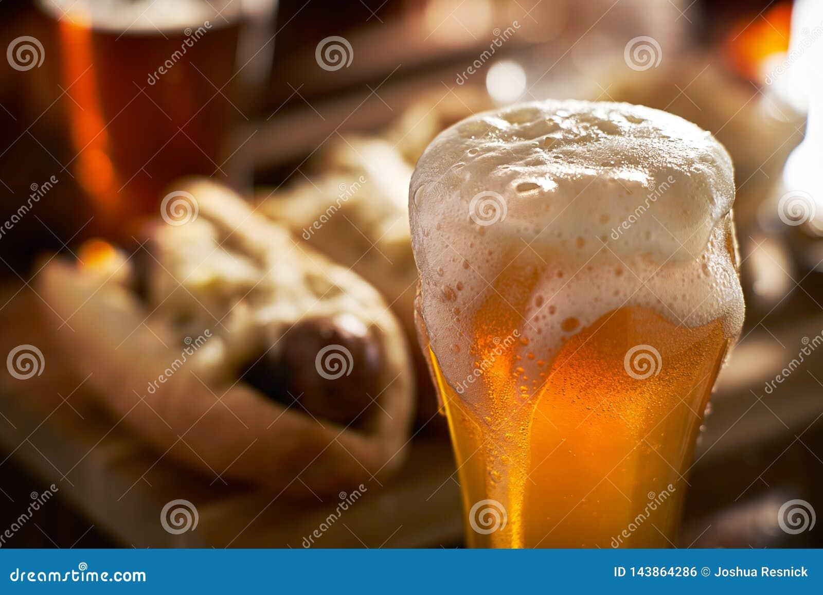 A fraîchement versé la bière ambre dans la tasse servie avec des bratwursts