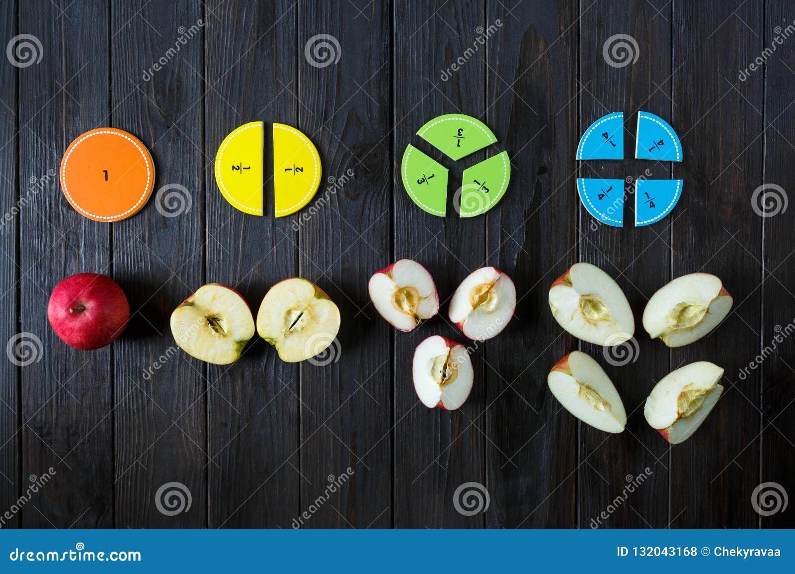 Fractions colorées de maths sur le fond ou la table en bois brun maths intéressantes pour des enfants Éducation, de nouveau au co