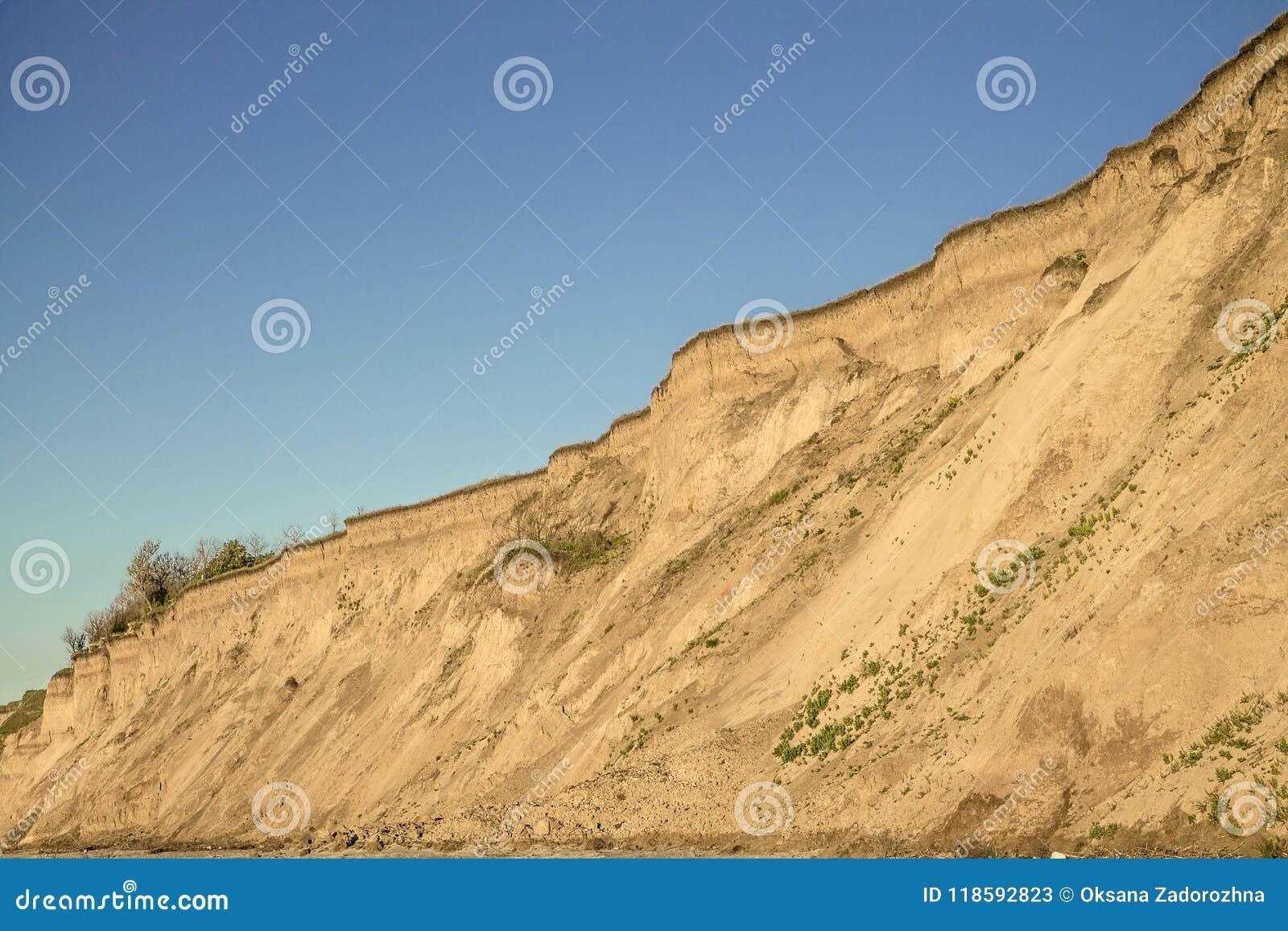Fractura vertical del suelo de arcilla de Sandy con las raíces de la planta y la pequeña vegetación aislada Cielo azul Costa de m