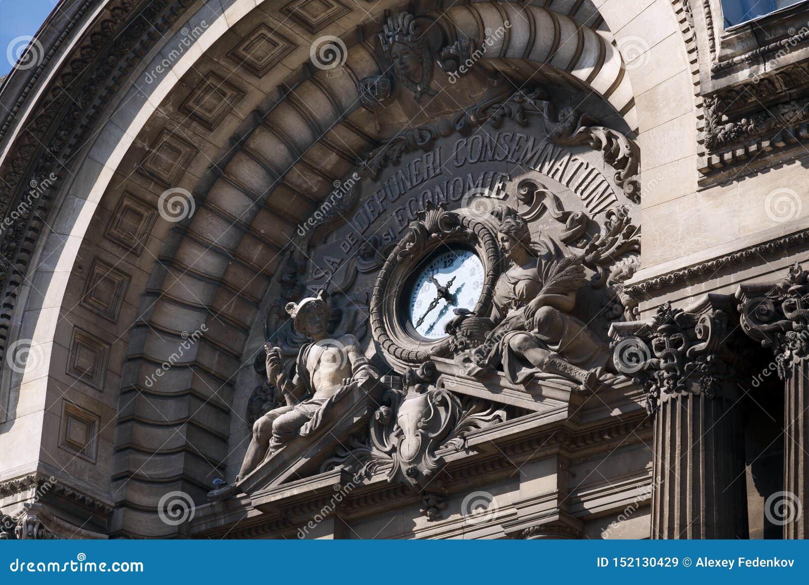 Fragment av arkitektoniska gränsmärken med en klocka och gammalgrekiskagudar på den gamla byggnaden av National Bank av Rumänien