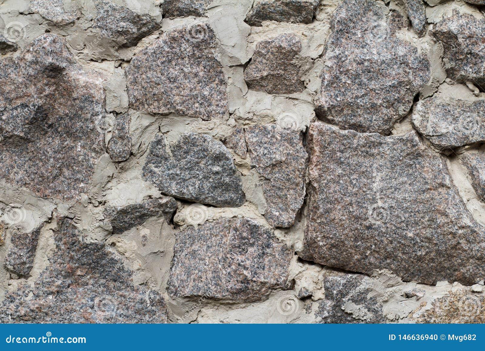 Fragment av den gr?a stenv?ggen med cementl?sningen Bekl?da besk?dar