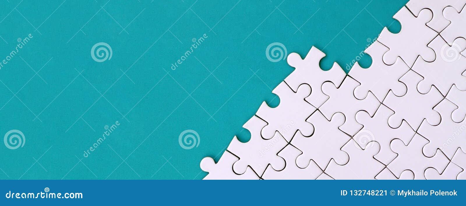 Fragment av ett vikt vitt pussel på bakgrunden av en blå plast- yttersida Texturfoto med kopieringsutrymme för text