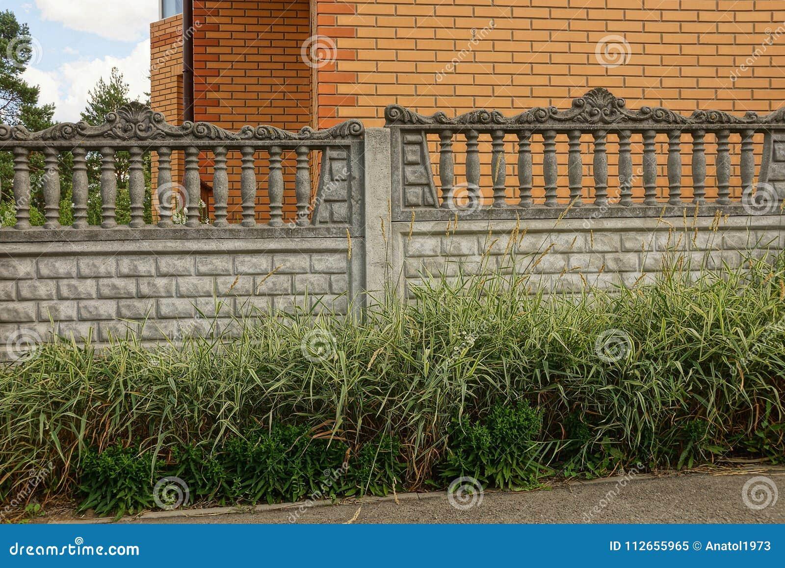 Fragment av grå färgbetongstaketet utanför i gräset