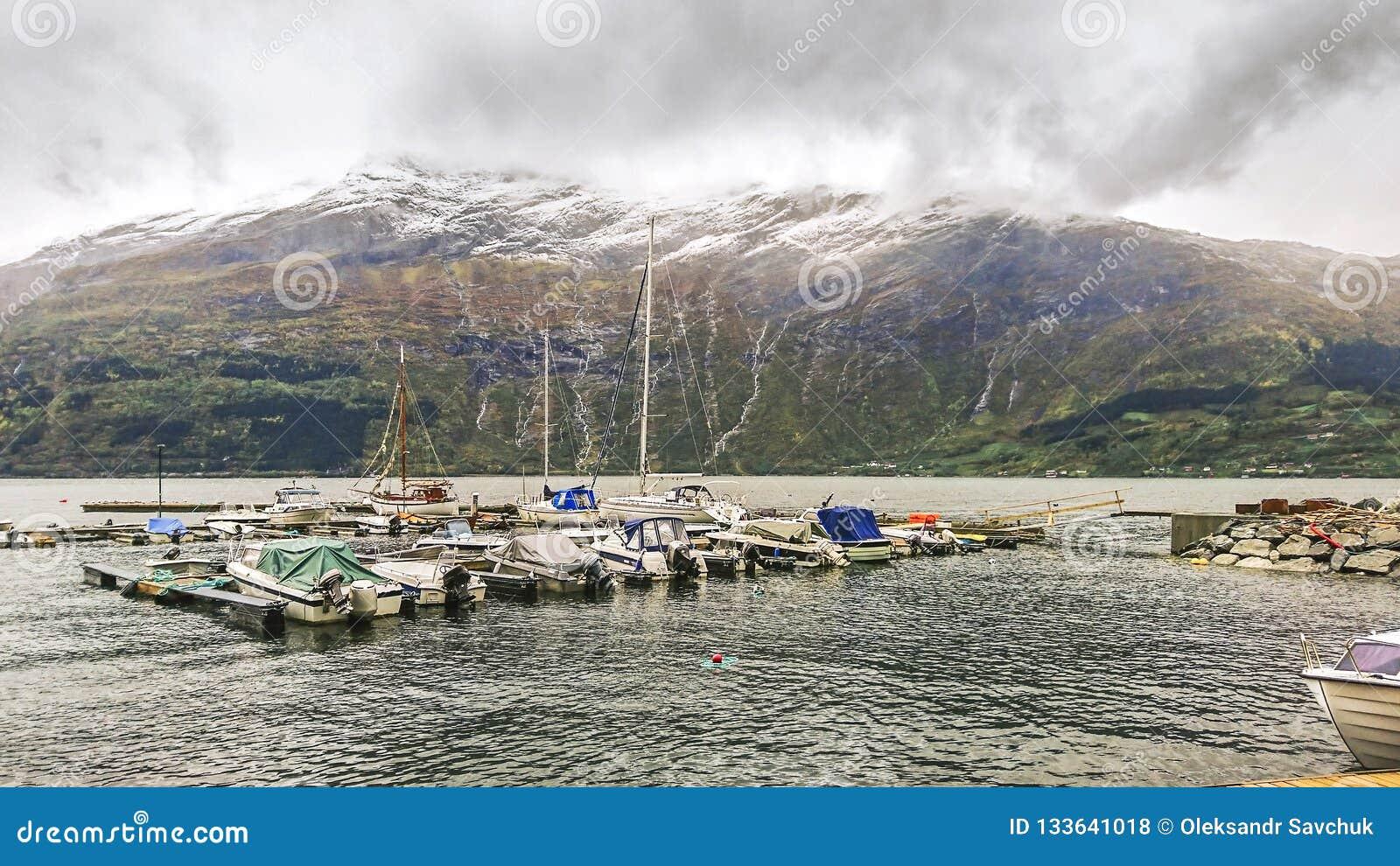 Fragment av pir i Surfjorden nära staden av Odda, Norge Sikt av den stora bergplatån med dess massiva glaciärer
