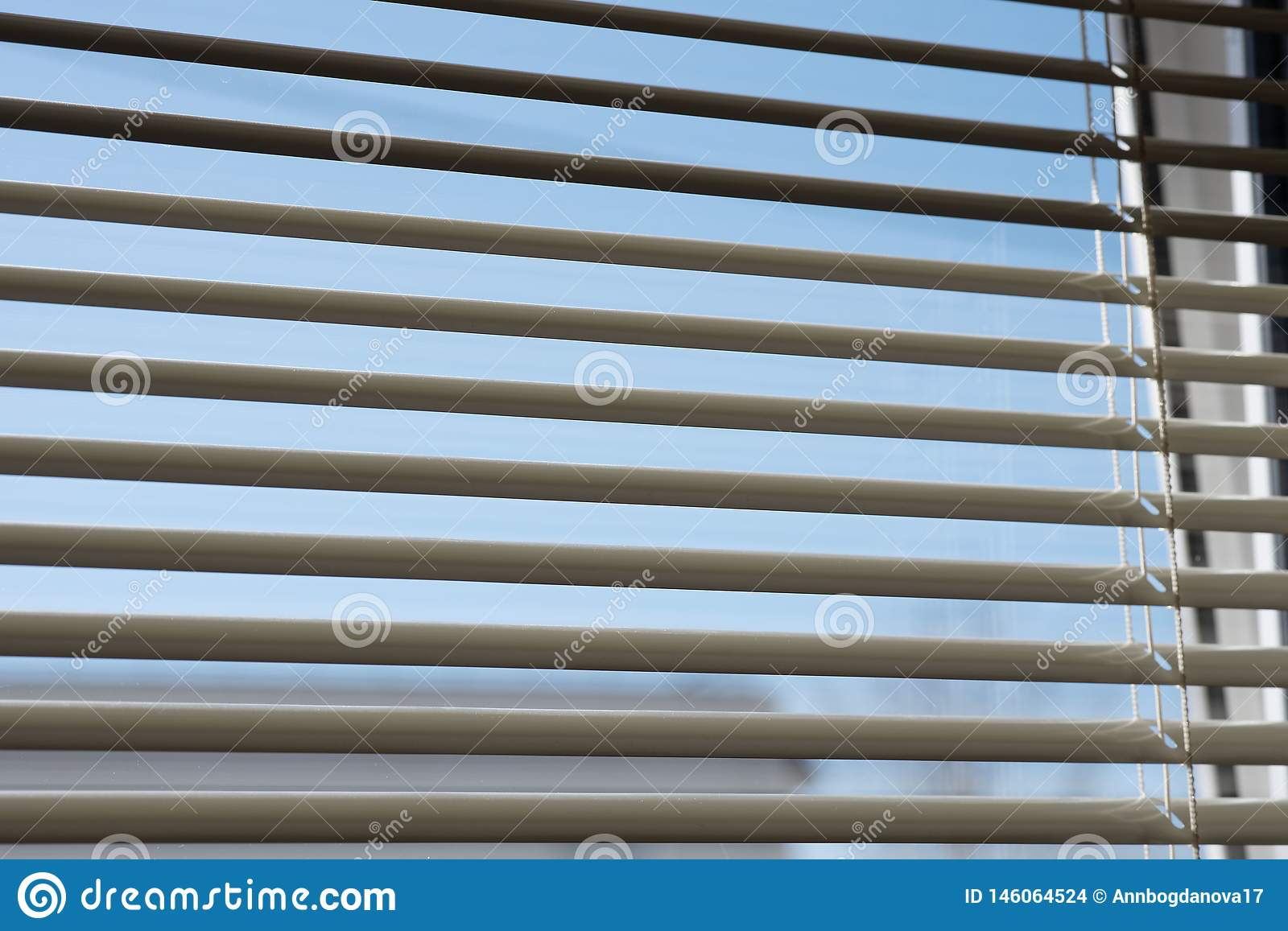 Fragment of blinds on the window. You can see the sky through the blinds