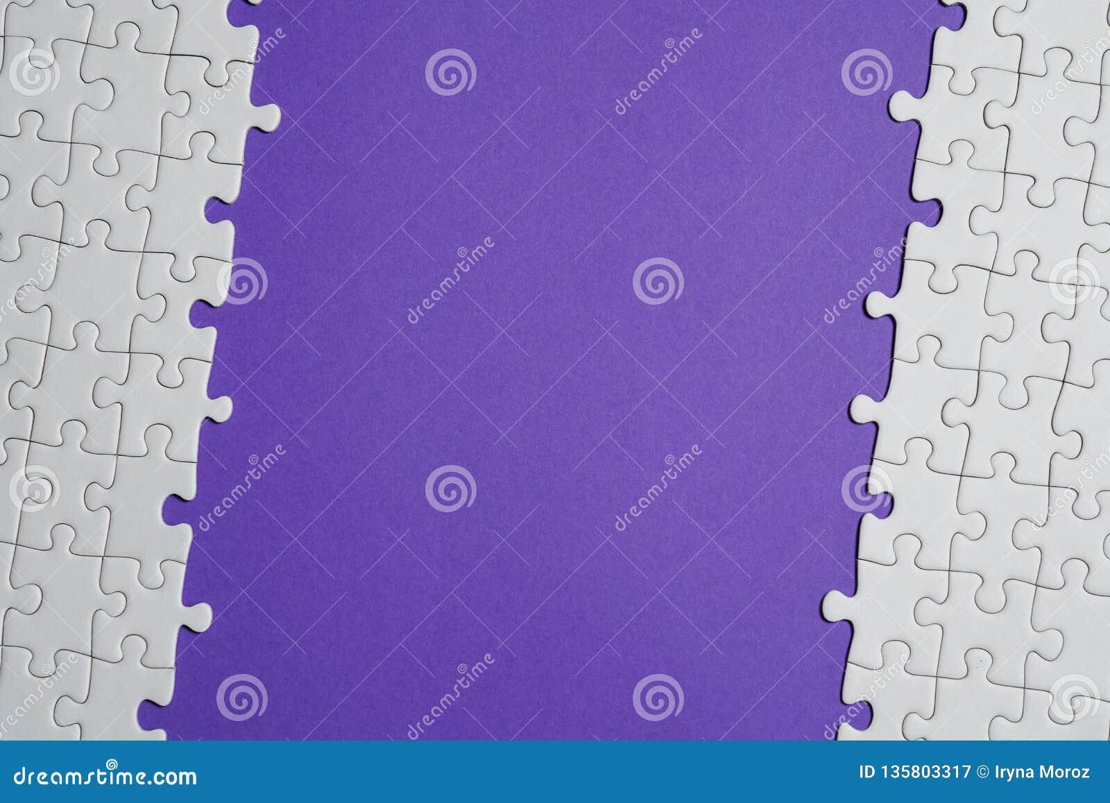Fragment d un puzzle denteux blanc plié et une pile des éléments mal peignés de puzzle dans la perspective d une surface violette