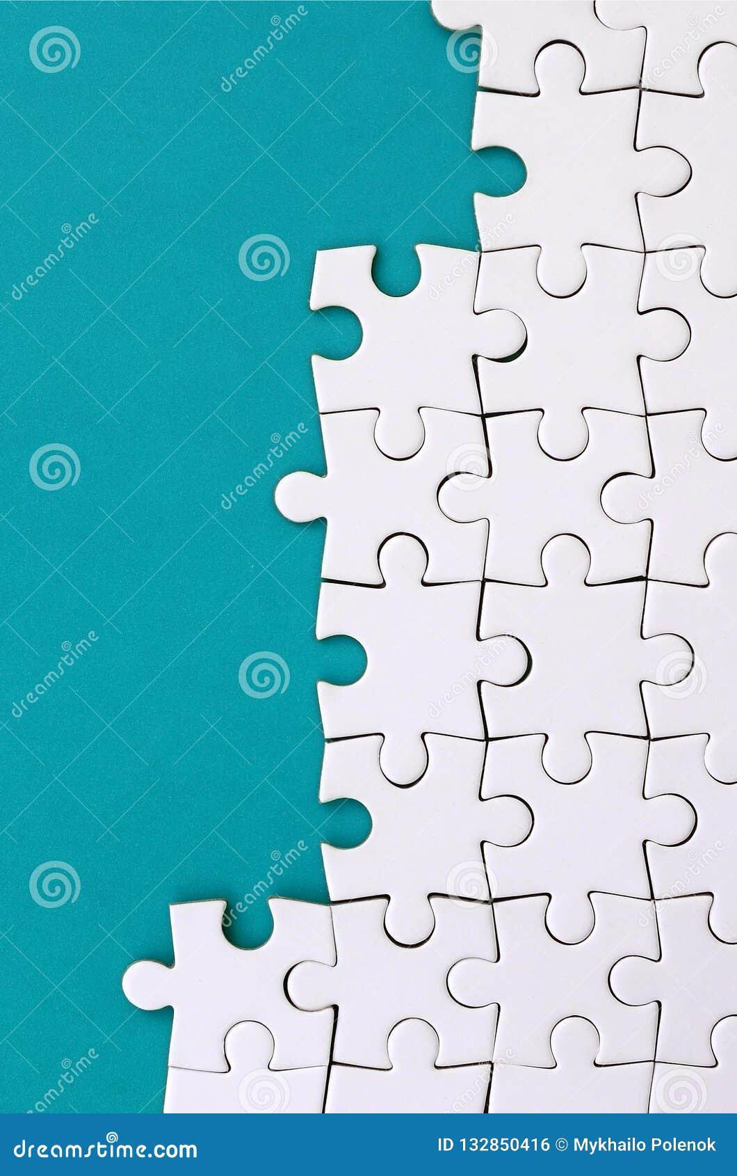Fragment d un puzzle denteux blanc plié sur le fond d une surface en plastique bleue Photo de texture avec l espace de copie pour