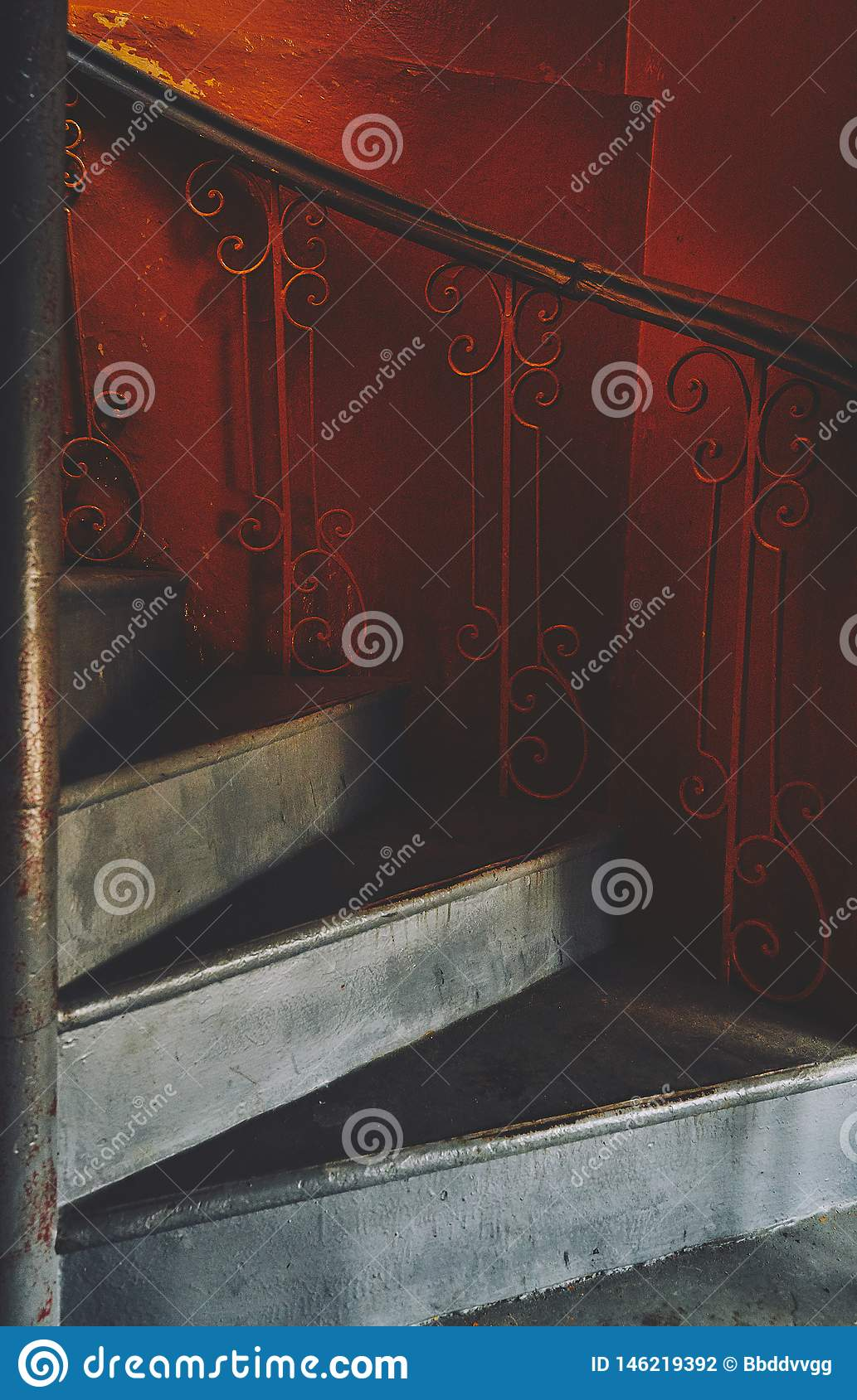 Fragment of a spiral gray staircase in an old orange train, in ocher style, of spirals and descending lines of steps