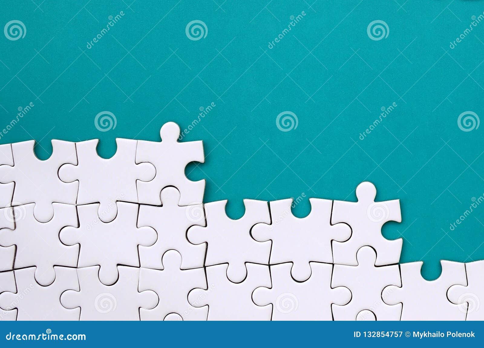 Fragment van een gevouwen witte puzzel op de achtergrond van een blauwe plastic oppervlakte Textuurfoto met exemplaarruimte voor
