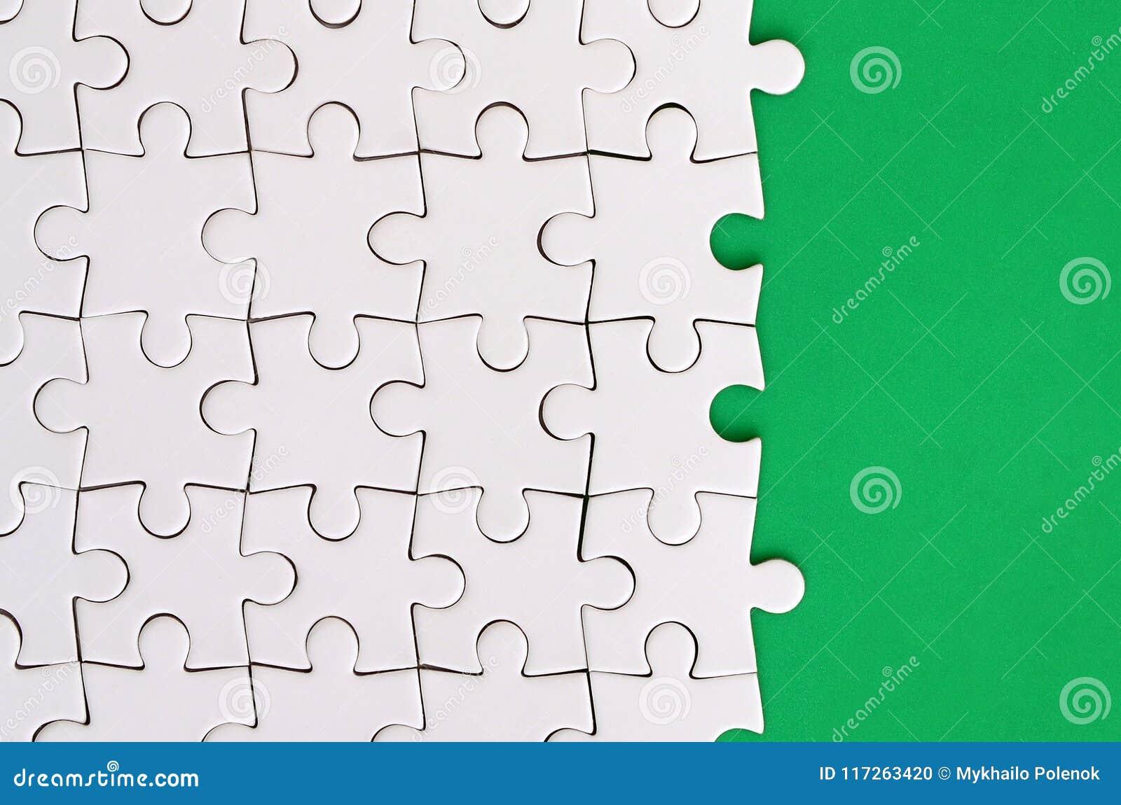 Fragment van een gevouwen witte puzzel op de achtergrond van een groene plastic oppervlakte Textuurfoto met exemplaarruimte voor