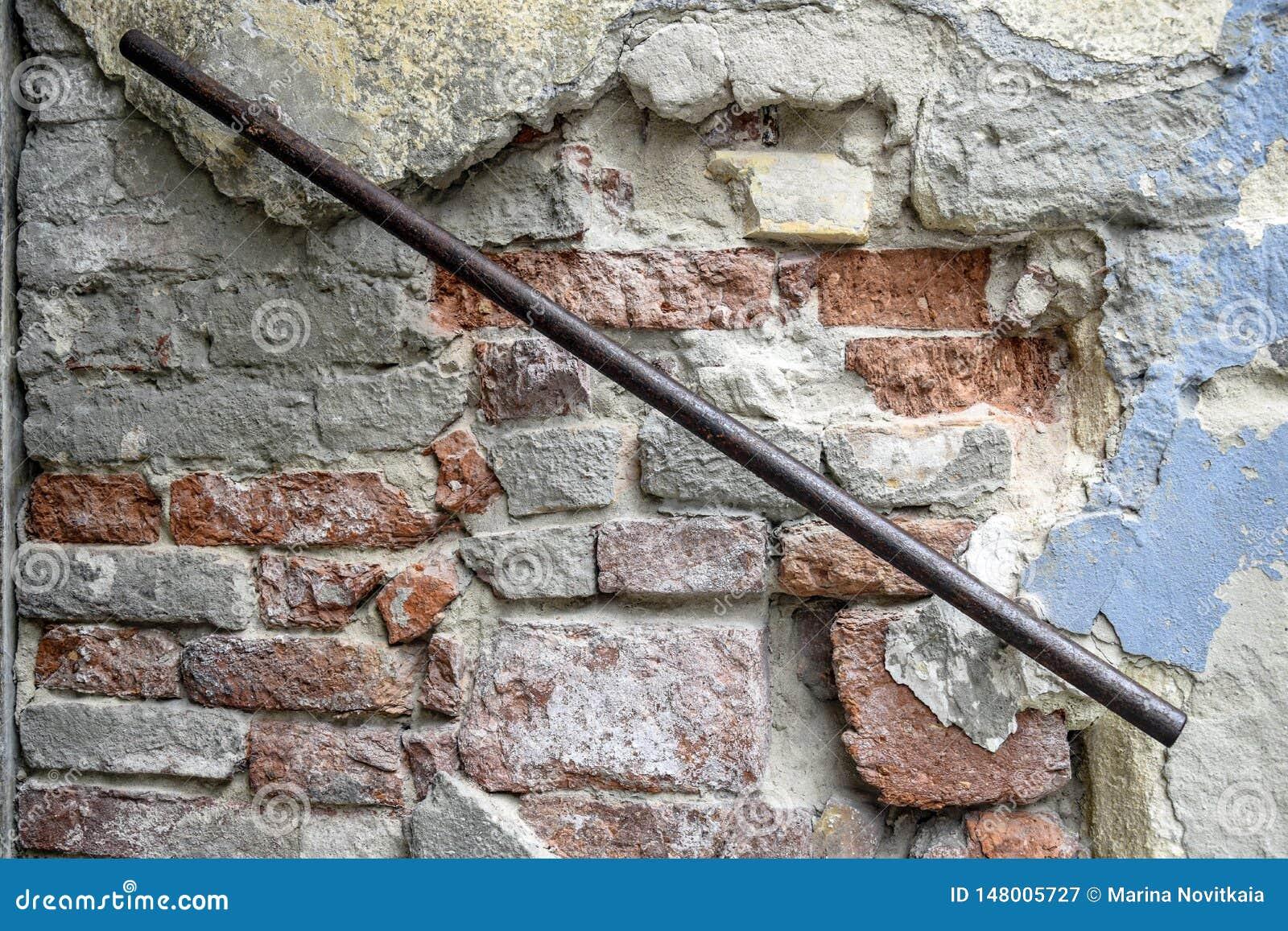 Fragment van een oude bakstenen muur met roestige ijzerleuning De textuur van het metselwerk