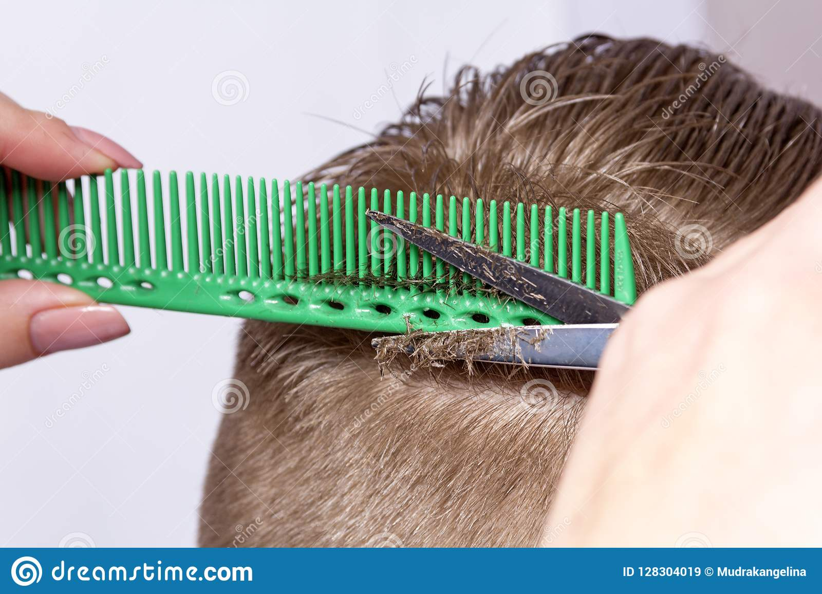 Fragment of the young man`s head during shearing with hairdressers scissors on blurred background of window