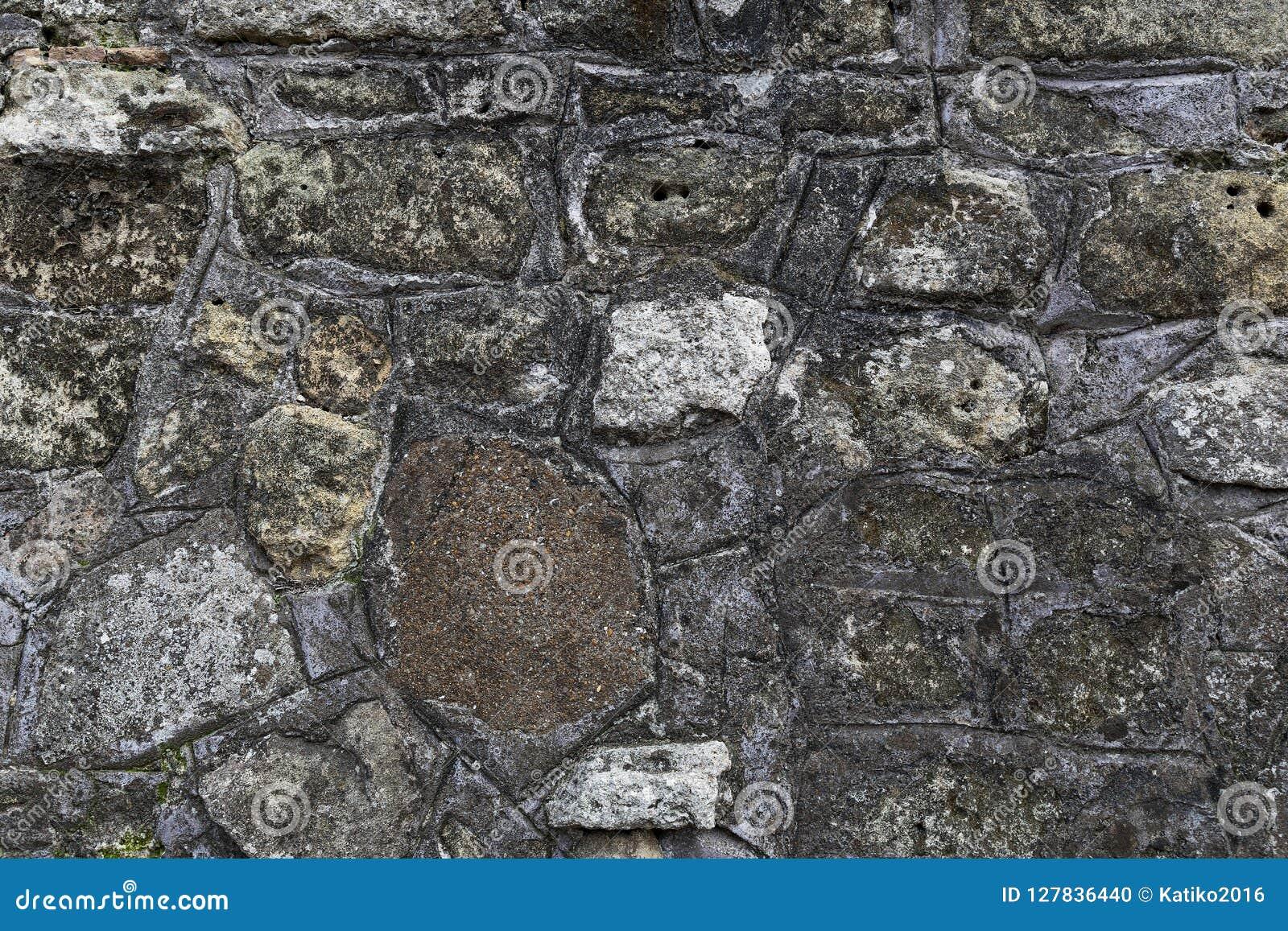 Fragmentet av den gamla gråa stenväggen som göras av olikt form och format, vaggar med grön mossa på det