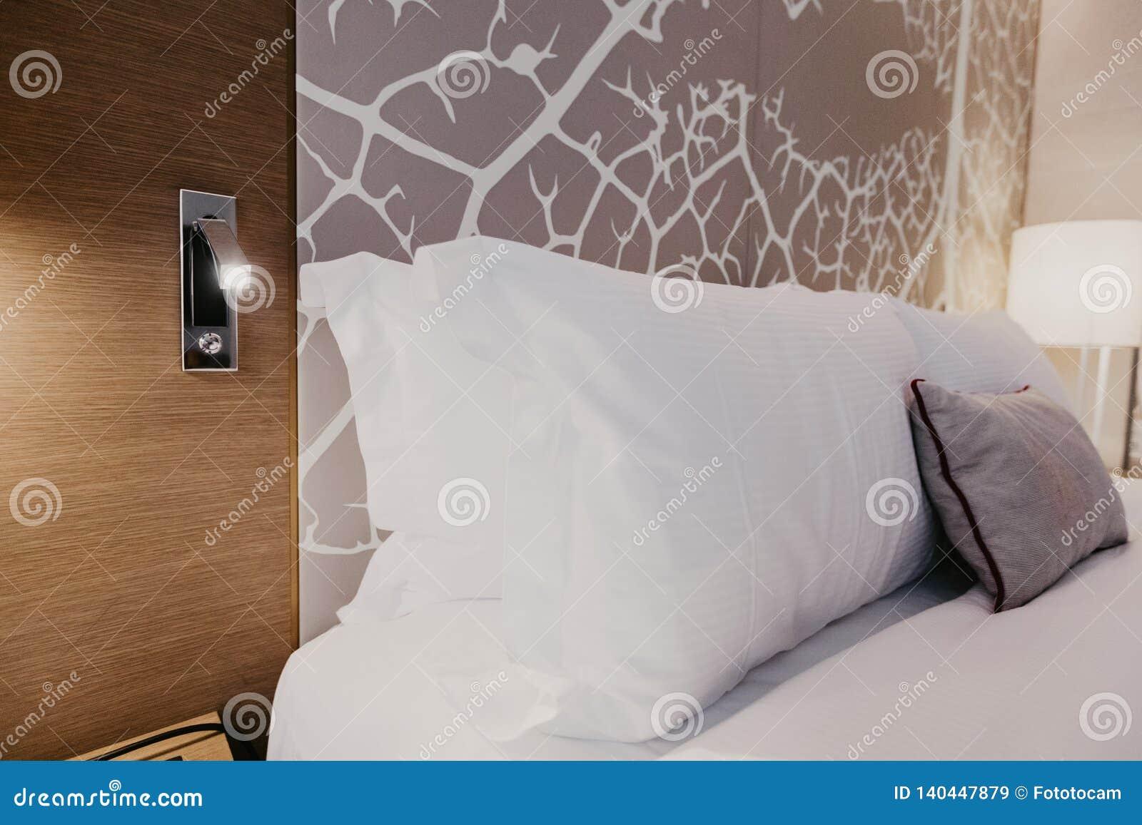 Fragmento ascendente cercano del dormitorio con la lámpara de lectura en hogar u hotel moderno