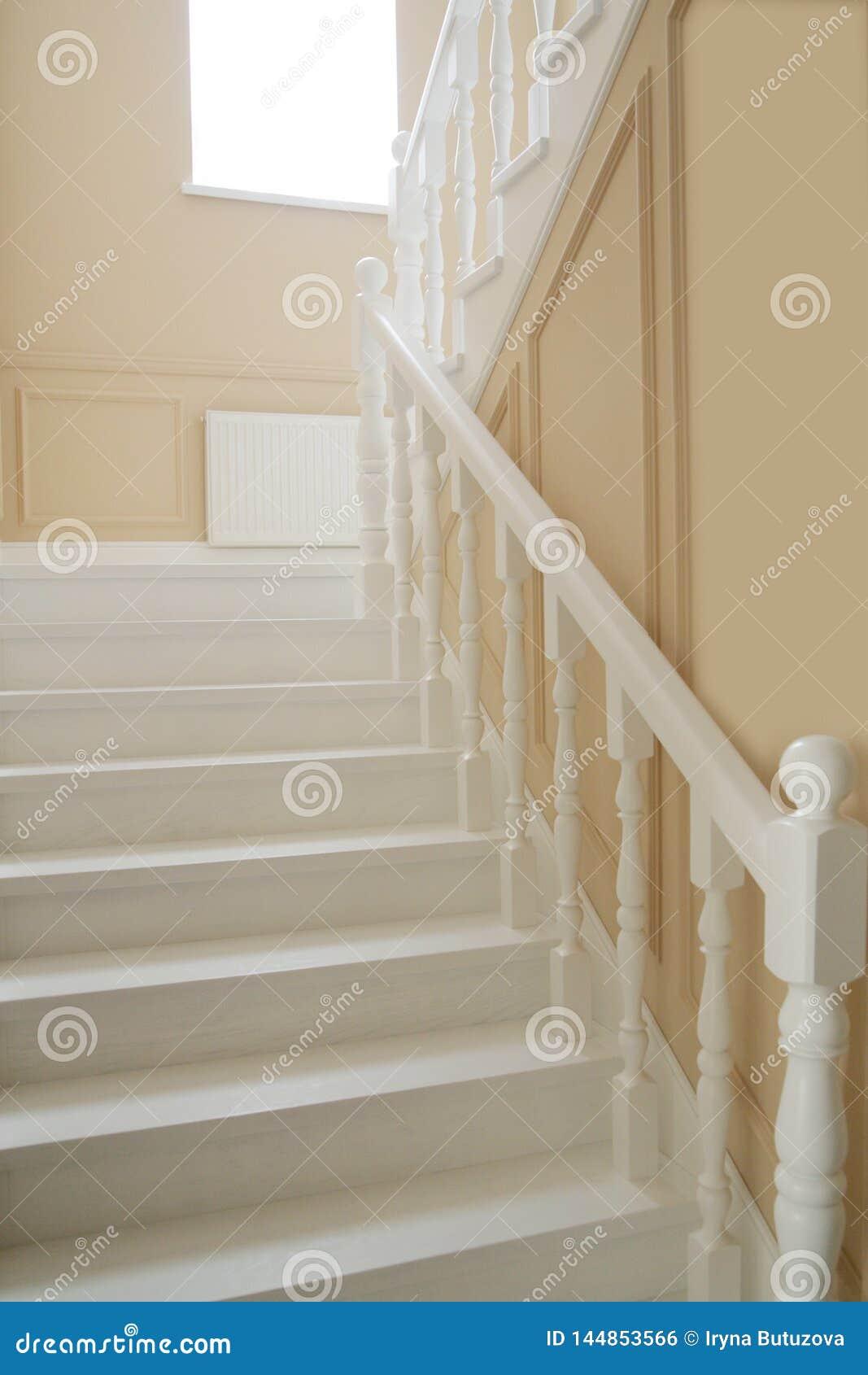 Fragmento das escadas brancas e de paredes bege