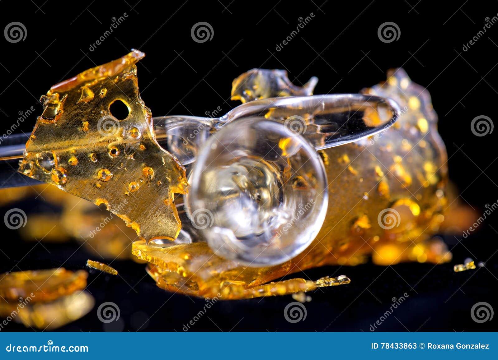 Fragmento del concentrado del aceite del cáñamo aka con las herramientas de cristal aisladas