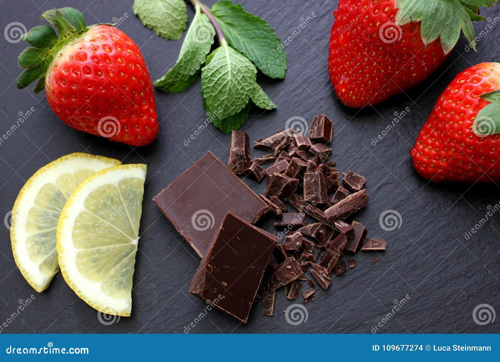 Fragole, fette del limone, foglie di menta e cioccolato nero sul fondo nero dell ardesia