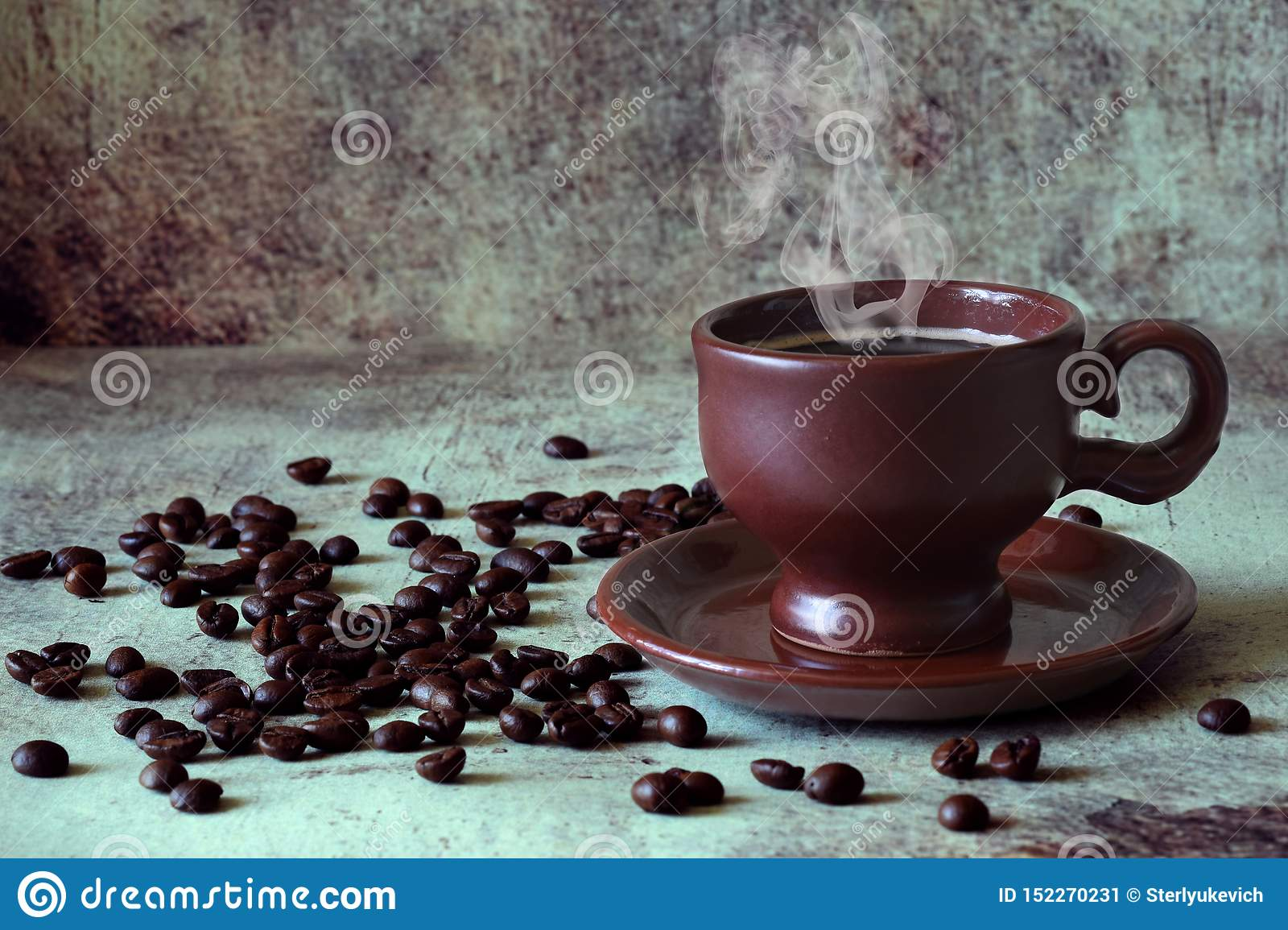 Fragrant hot coffee in a beautiful clay Cup among the scattered coffee beans