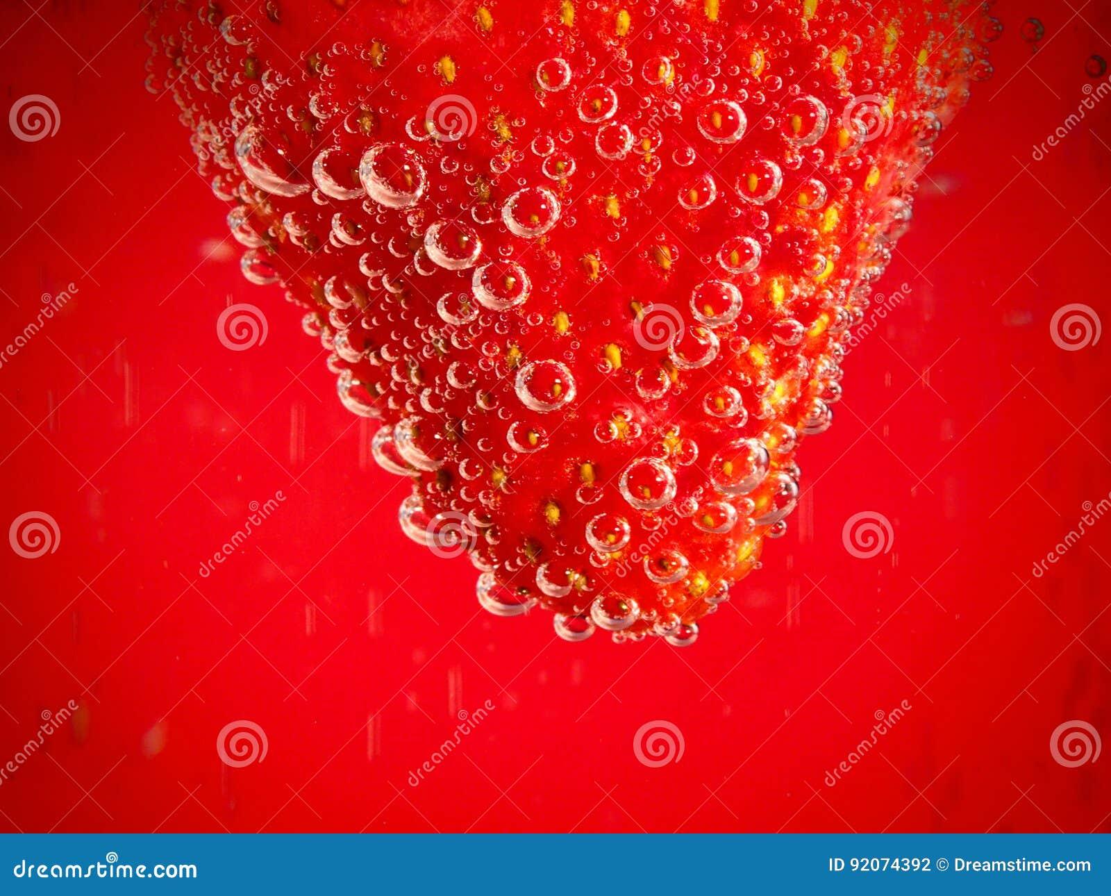 Fraise sur le fond rouge avec des bulles