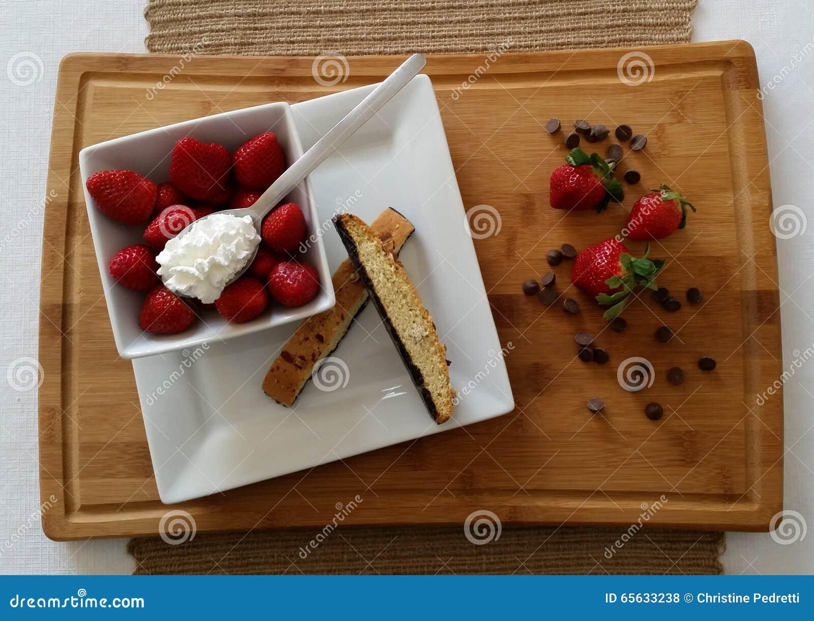Fraises avec le biscotti, la crème fouettée et les puces de chocolat