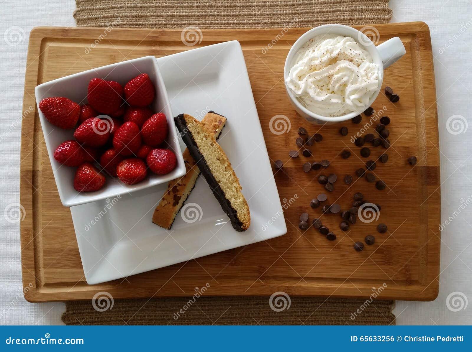 Fraises avec le biscotti, le chocolat chaud et les pommes chips de chocolat