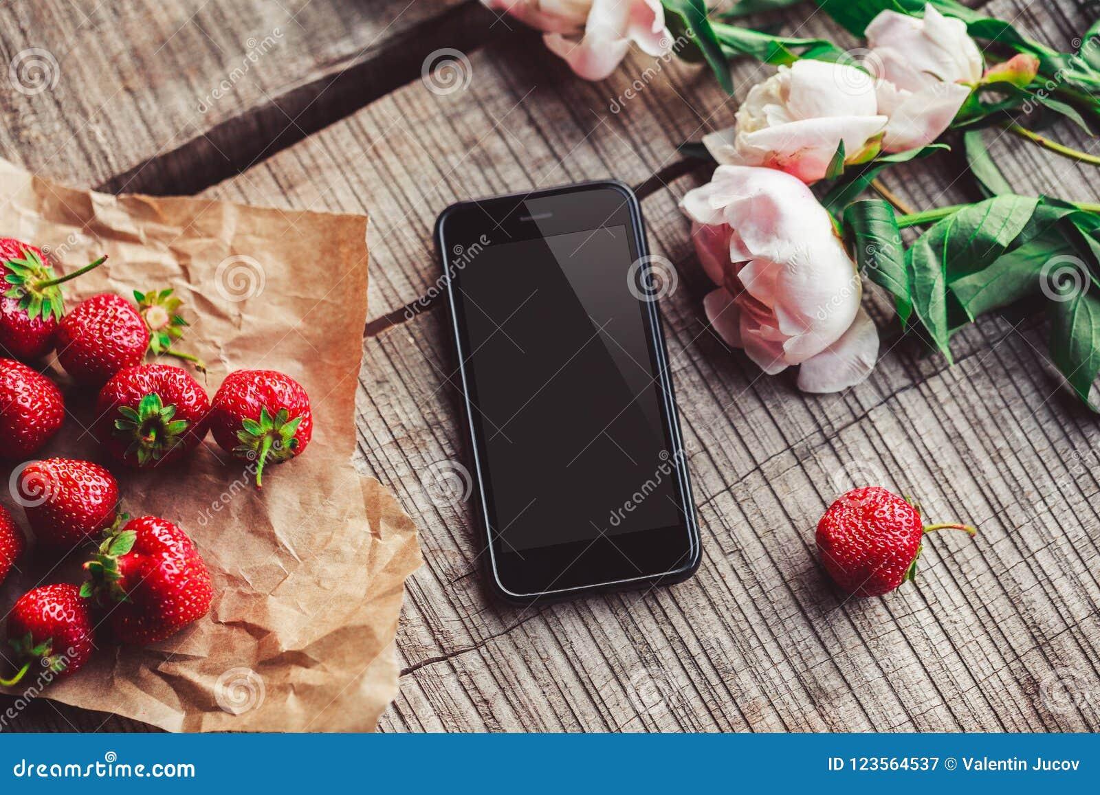 Fraises, fleurs et téléphone sur la table rustique Petit déjeuner sain, consommation propre, concept de nourriture de vegan
