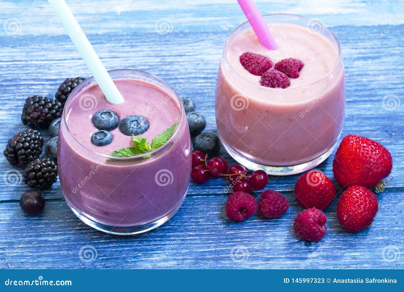Framboesa, morango, batido do mirtilo no fundo de madeira azul Milk shake com bagas frescas batido de fruta com