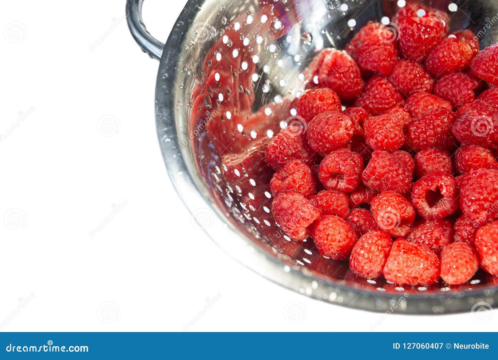 Framboise rouge fraîche et humide délicieuse dans une passoire pour le lavage