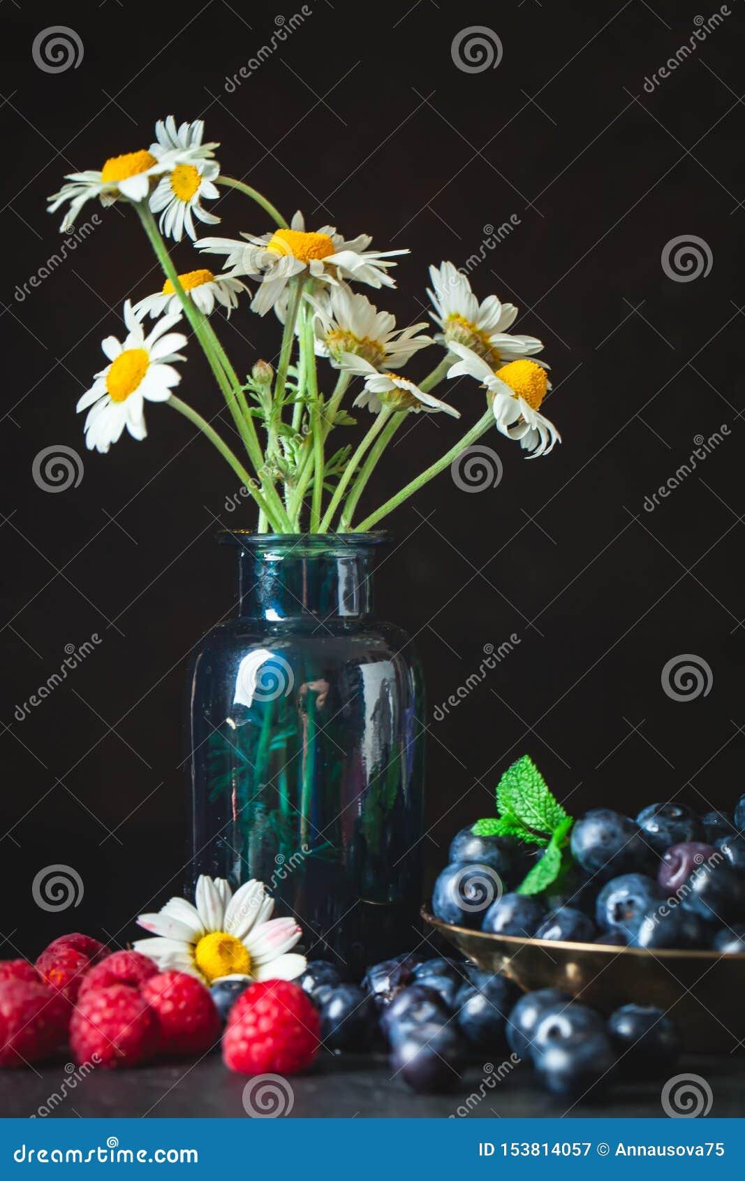 Framboises et myrtilles avec la camomille et les feuilles sur un fond foncé ?t? et concept sain de nourriture Fond
