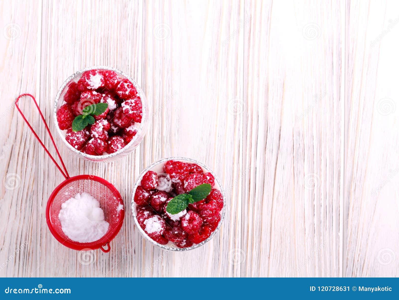Framboos gelaagd die dessert in glazen wordt gediend