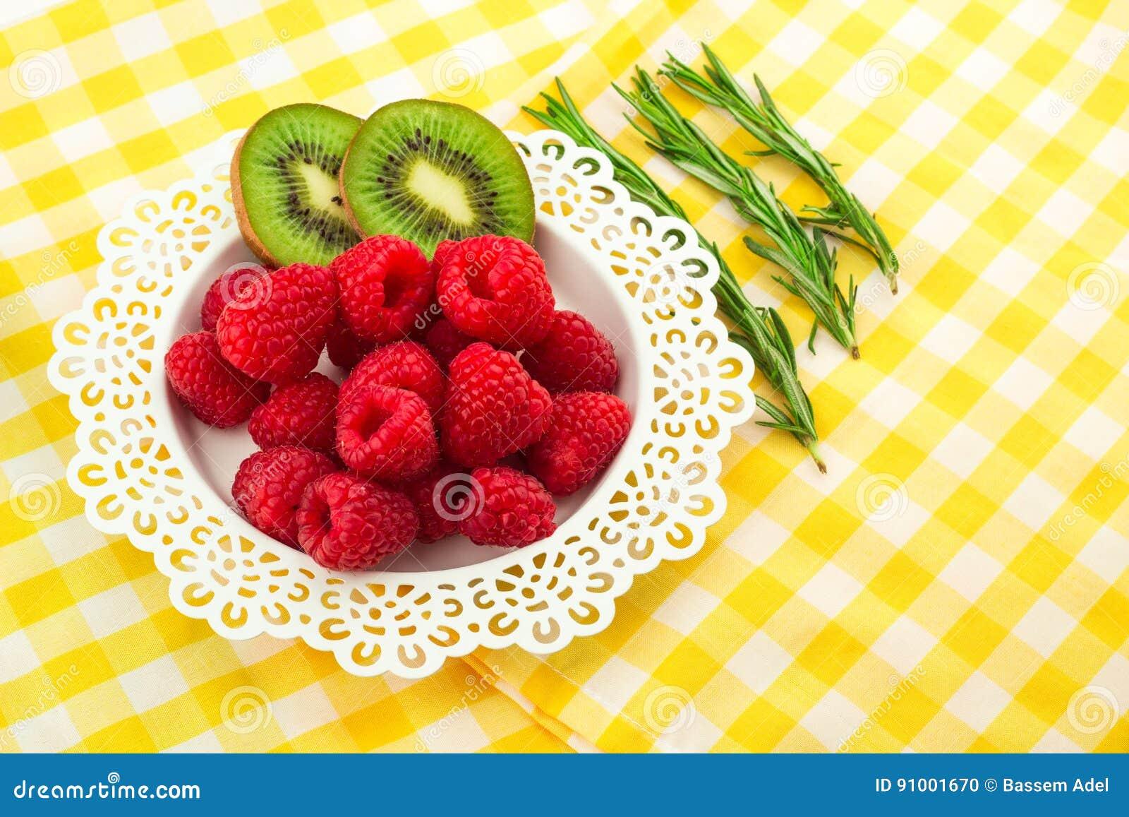 Frambuesas rojas frescas en una placa artística blanca