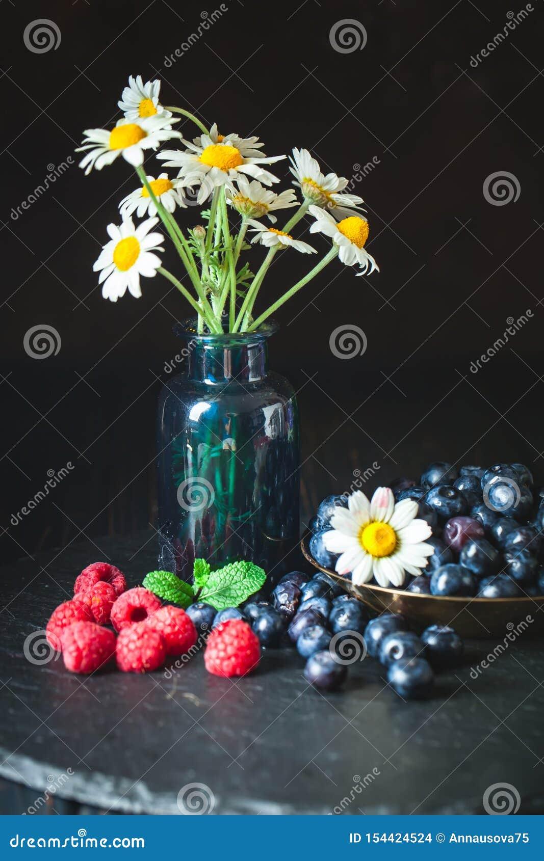 Frambuesas y arándanos con la manzanilla y las hojas en un fondo oscuro Verano y concepto sano de la comida Fondo