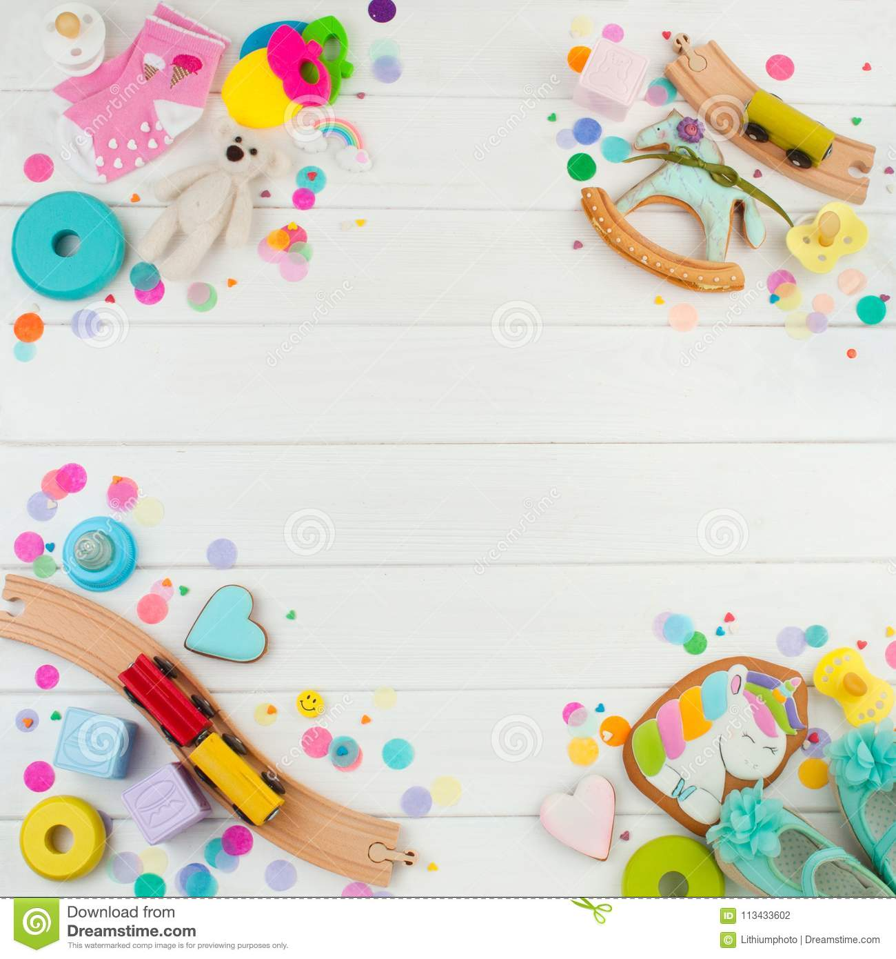 Frame from baby accessories and toys on white wooden background