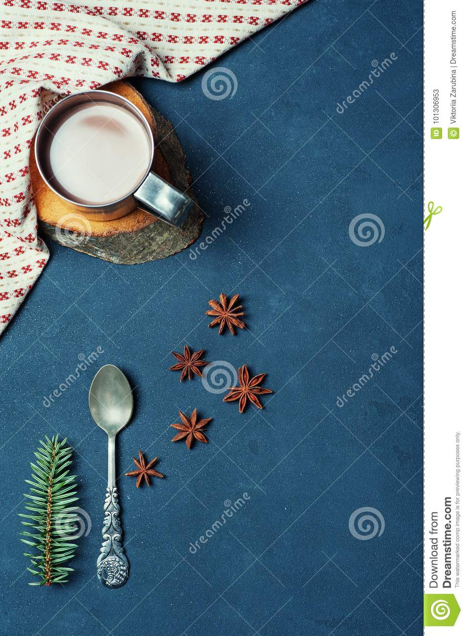 Frame of Cup of Cacao Coffee Beans Cinnamon sticks Spoon and Fir Branch on Dark Texture Table decorated Napkin. Kitchen Ingredient