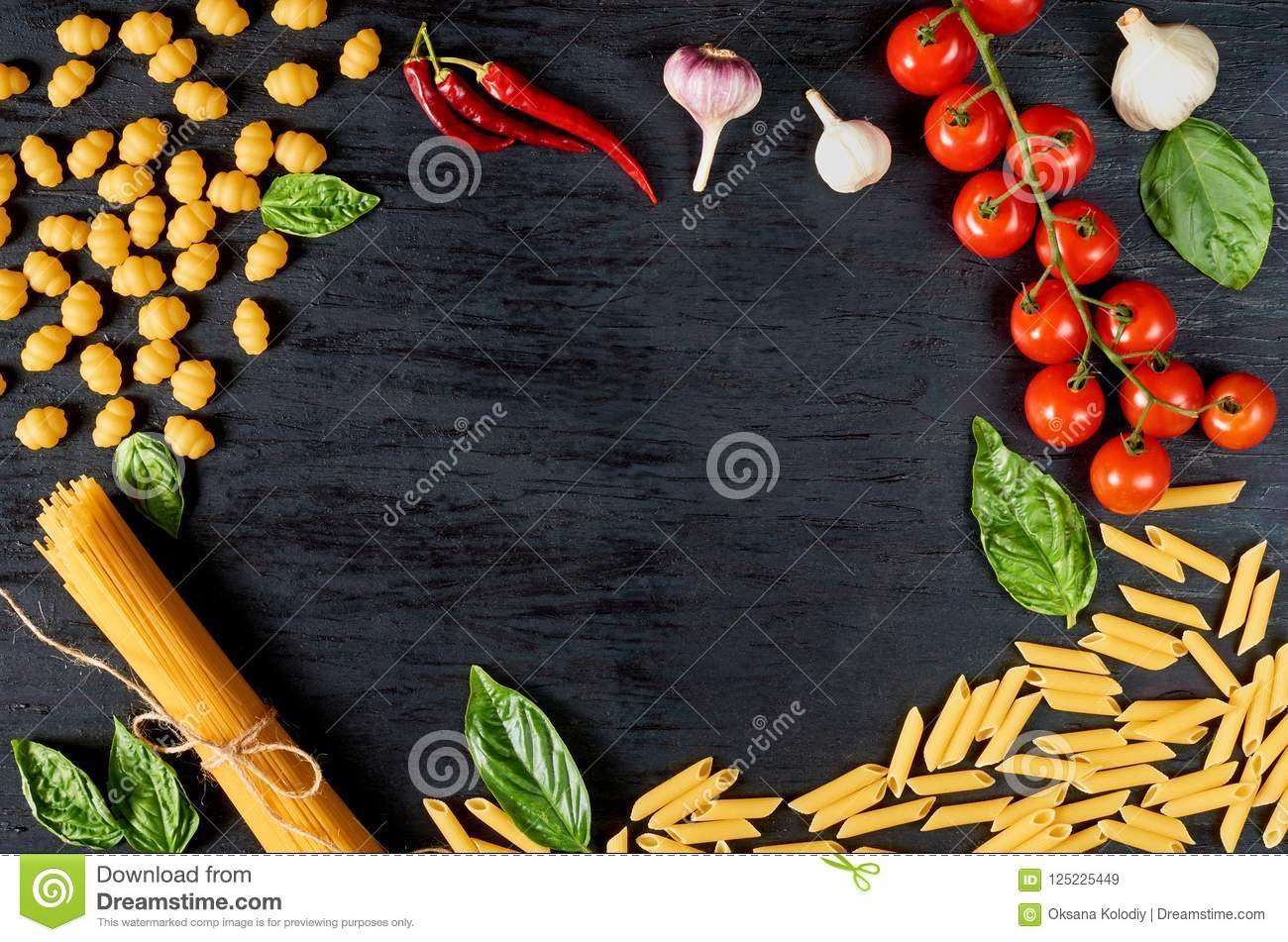 Frame of Italian traditional food, spices and ingredients for cooking as basil, cherry tomatoes, chili pepper, garlic and pasta
