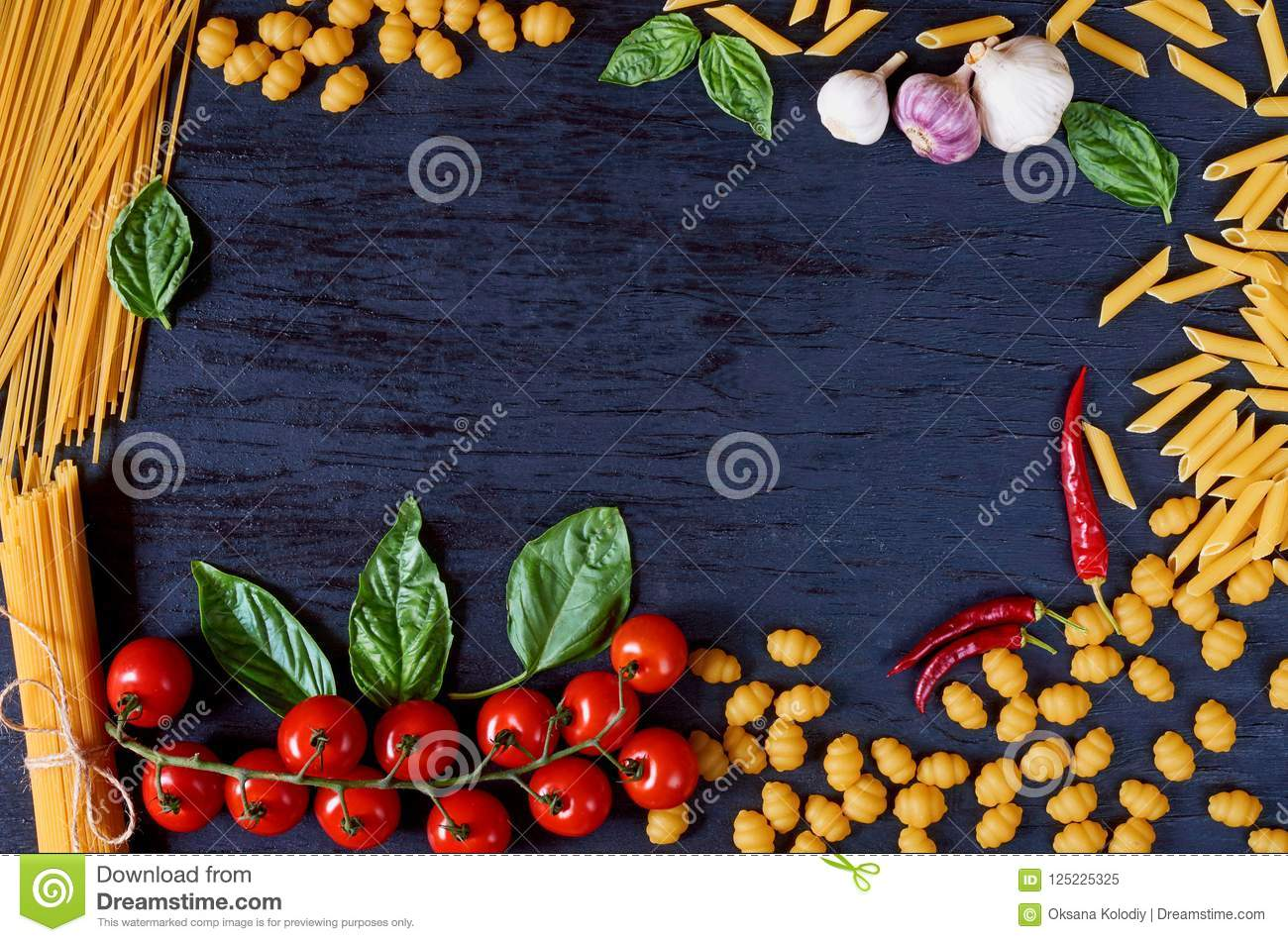 Frame of Italian traditional food, spices and ingredients for cooking as basil, cherry tomatoes, garlic and various pasta