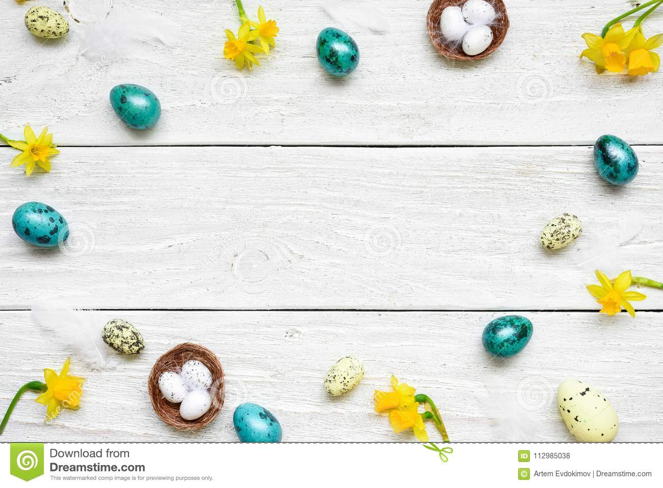 Frame made of easter eggs and spring flowers on white wooden background. easter composition