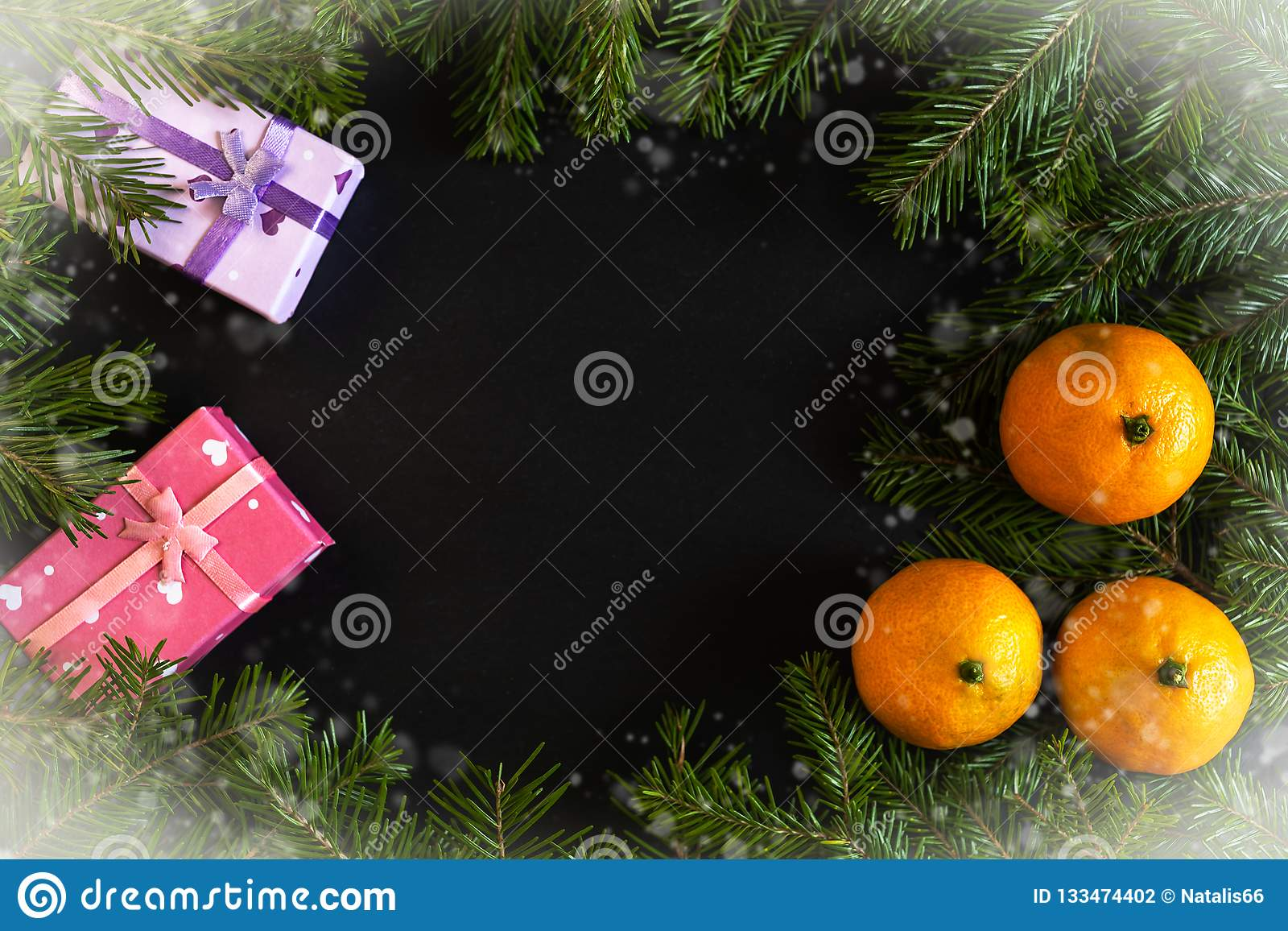 Frame of snow-covered fir branches, orange mandarins, gift boxes with dark copy space in middle