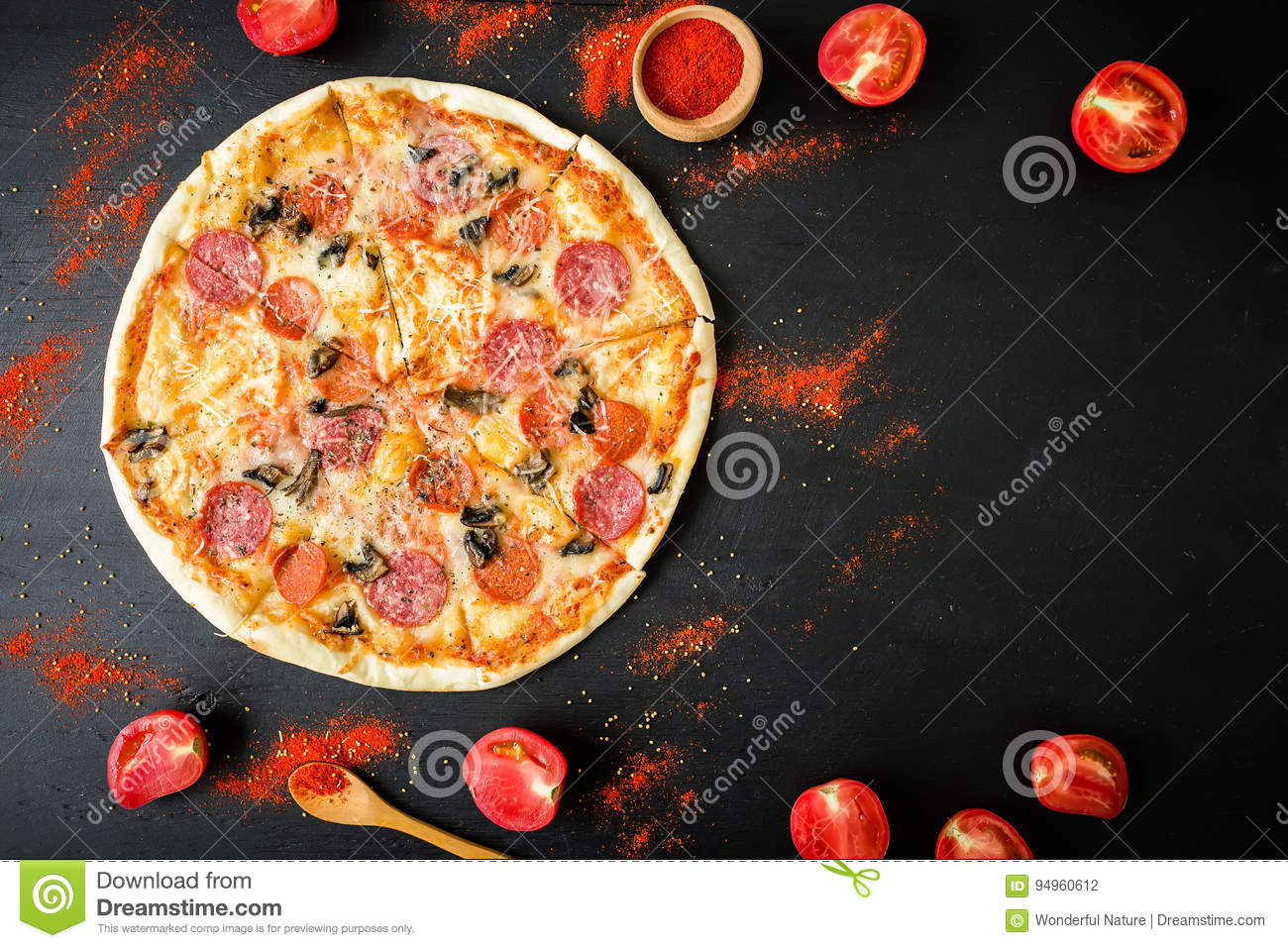 Frame of tasty Italian pizza with ingredients and spices on dark background. Flat lay, top view.
