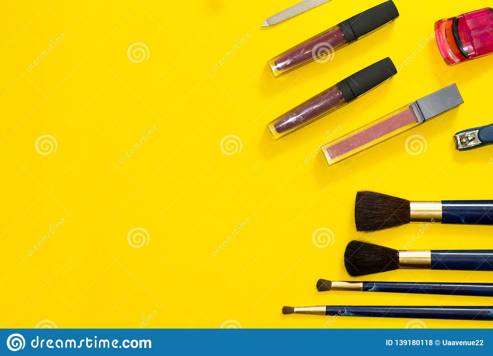 Frame of tools for makeup with copy space. Closeup woman`s accessories on yellow background: disposable pink razor, nail file,