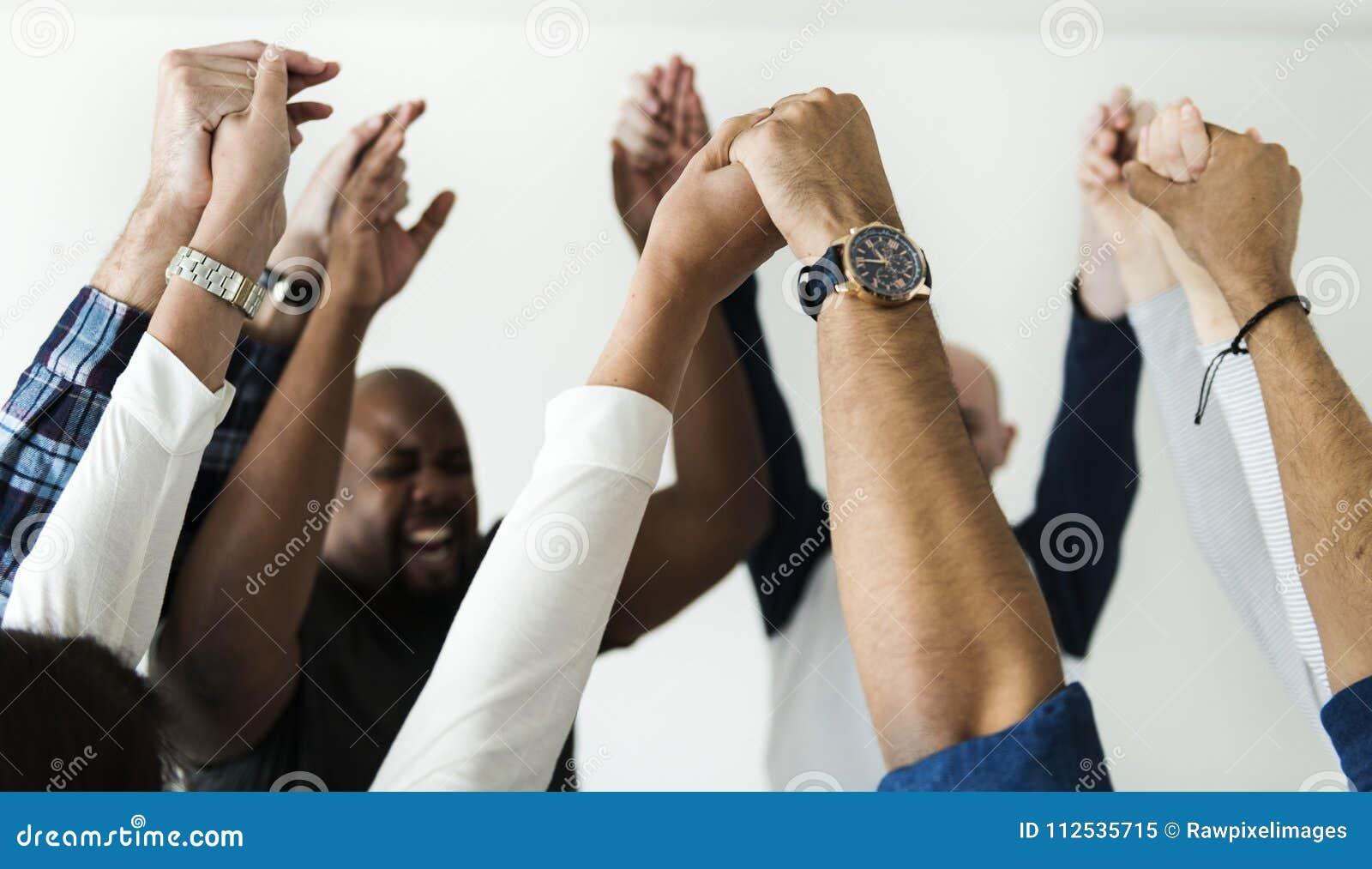 Framgång för händer för olikt folk sammanfogande tillsammans och berömbegrepp