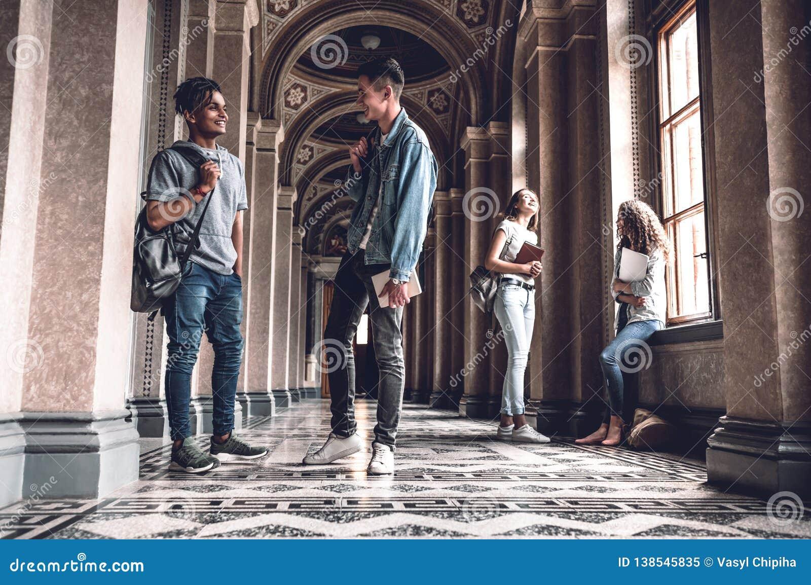 Framgång och kunskap hjälper oss på examen Lyckliga unga studenter som står på korridoren och prata för universitet